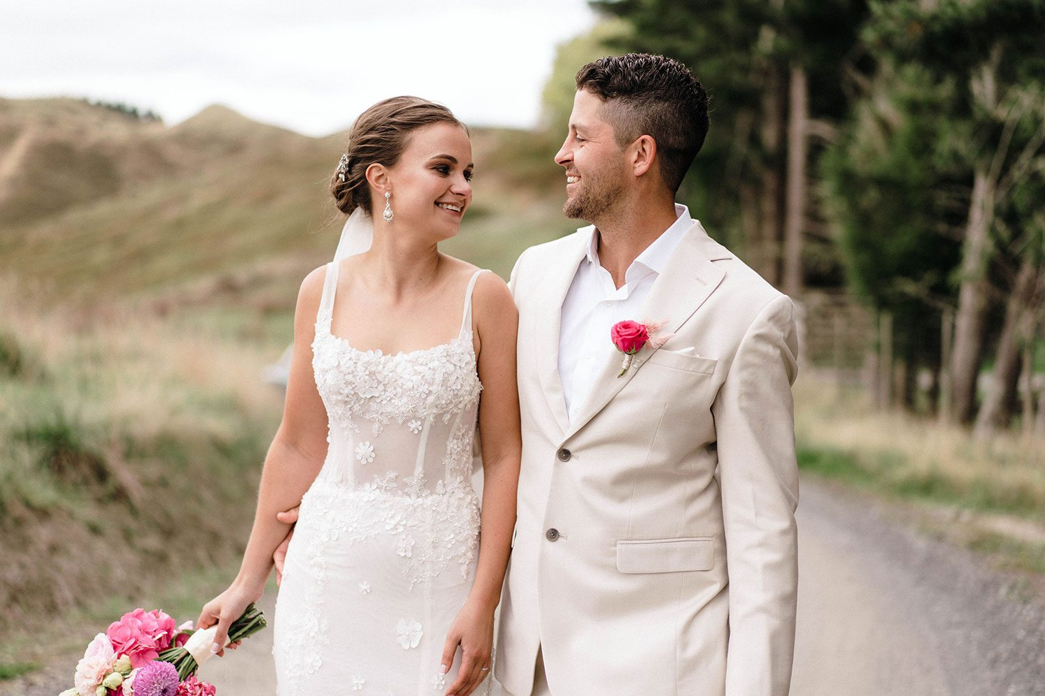 Bride wears bespoke E'More lace gown with boned bodice with hand beaded flower applique and full lace train by Auckland wedding dress maker Vinka designs - with groom looking at each other