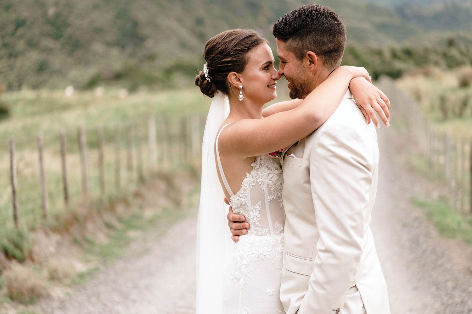 Bride wears bespoke E'More lace gown with boned bodice with hand beaded flower applique and full lace train by Auckland wedding dress maker Vinka designs - embrace with groom close up