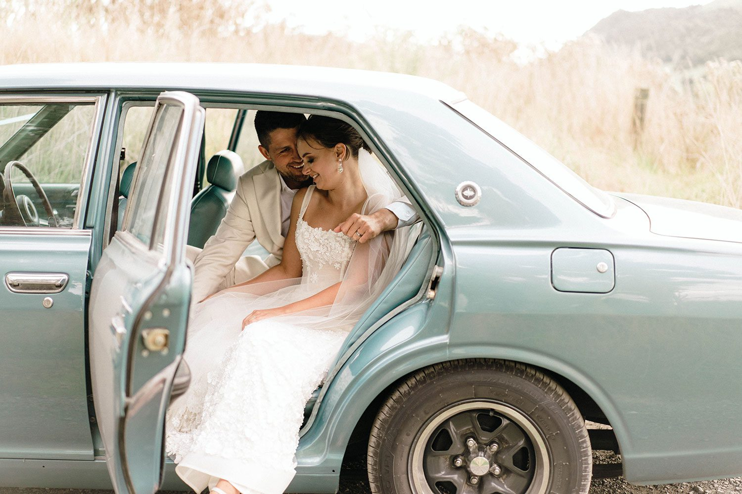 Bride wears bespoke E'More lace gown with boned bodice with hand beaded flower applique and full lace train by Auckland wedding dress maker Vinka designs - with groom in vintage car
