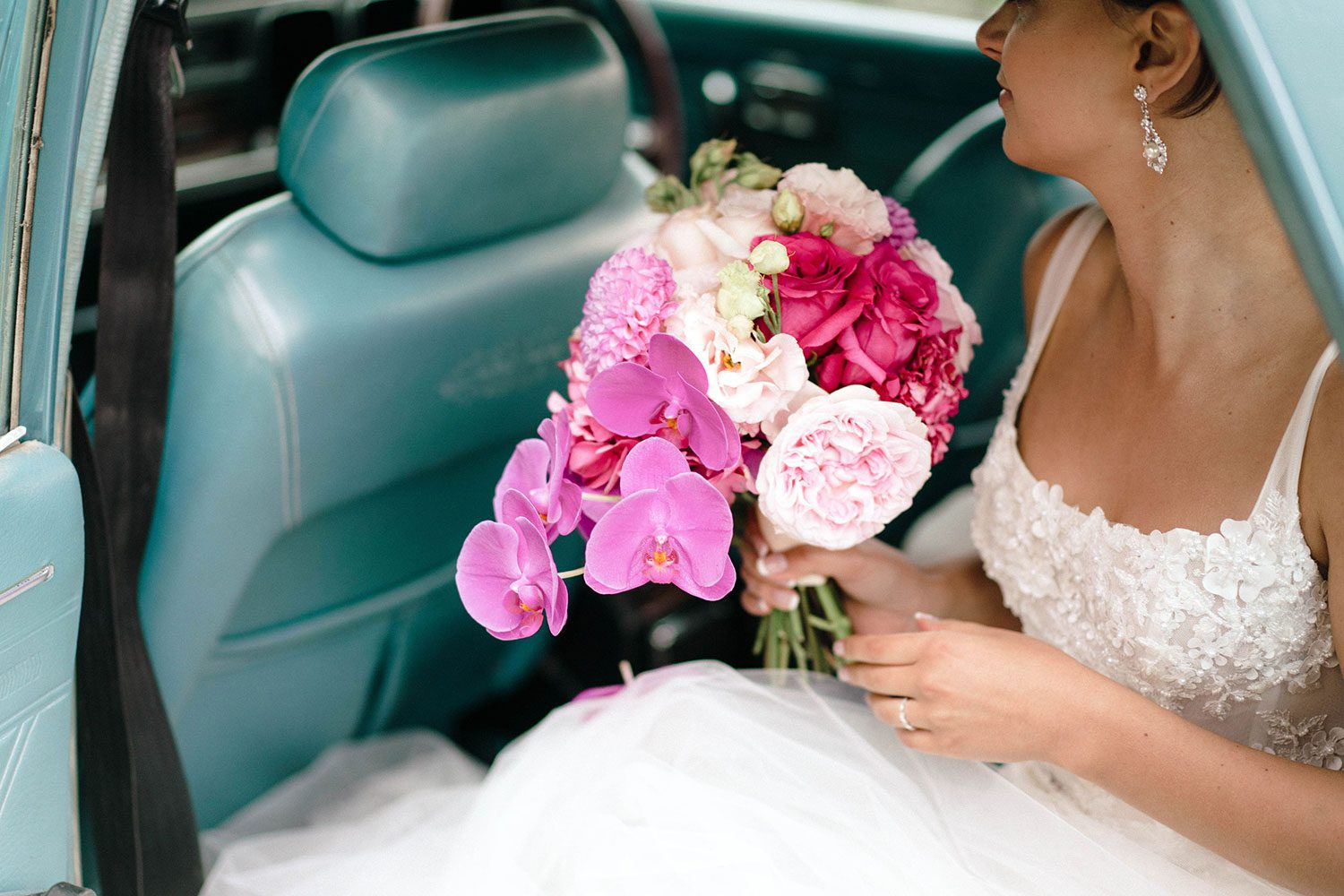 Bride wears bespoke E'More lace gown with boned bodice with hand beaded flower applique and full lace train by Auckland wedding dress maker Vinka designs - with bouquet in vintage car