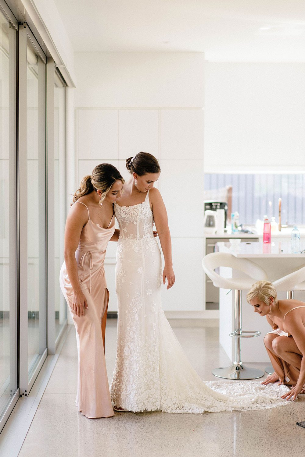 Bride wears bespoke E'More lace gown with boned bodice with hand beaded flower applique and full lace train by Auckland wedding dress maker Vinka Designs - getting ready with bridesmaids