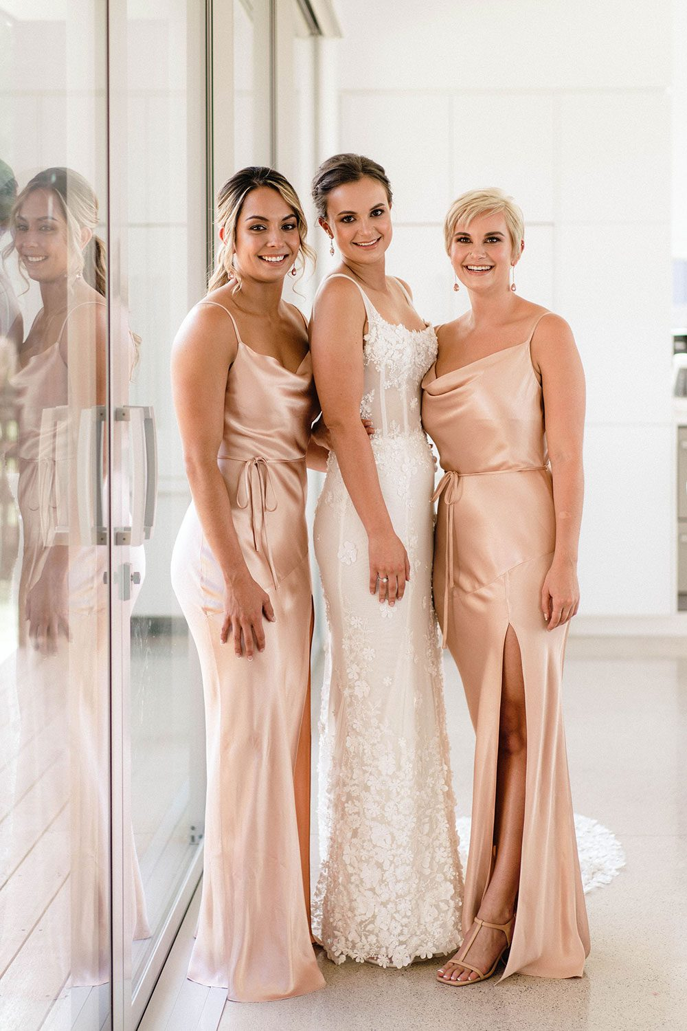 Bride wears bespoke E'More lace gown with boned bodice with hand beaded flower applique and full lace train - with bridesmaids near window