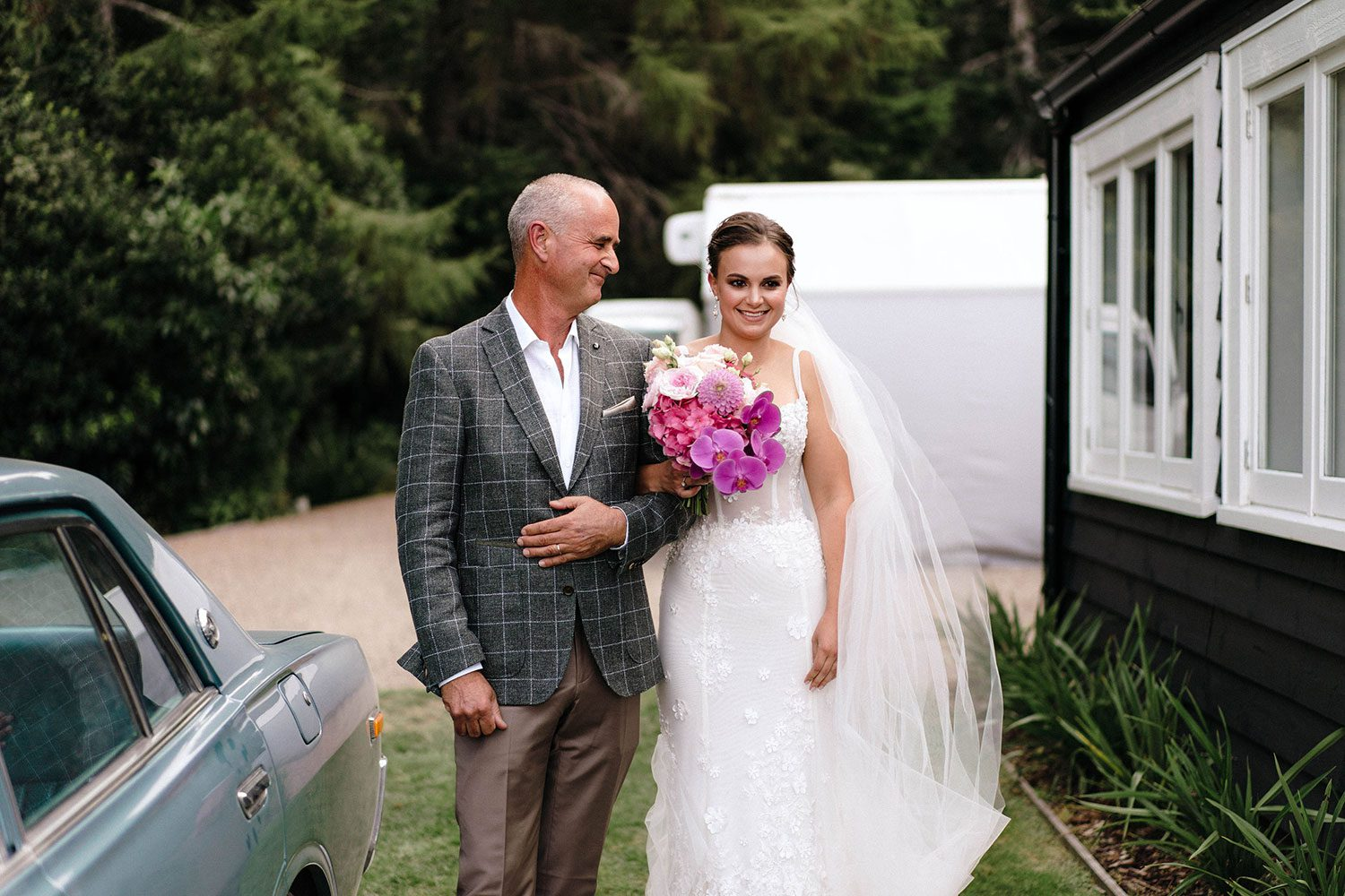 Bride wears bespoke E'More lace gown with boned bodice with hand beaded flower applique and full lace train by Auckland wedding dress maker Vinka Designs - with father