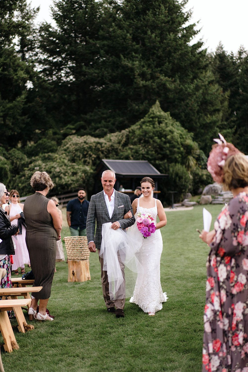 Bride wears bespoke E'More lace gown with boned bodice with hand beaded flower applique and full lace train by Auckland wedding dress maker Vinka designs - walking down aisle