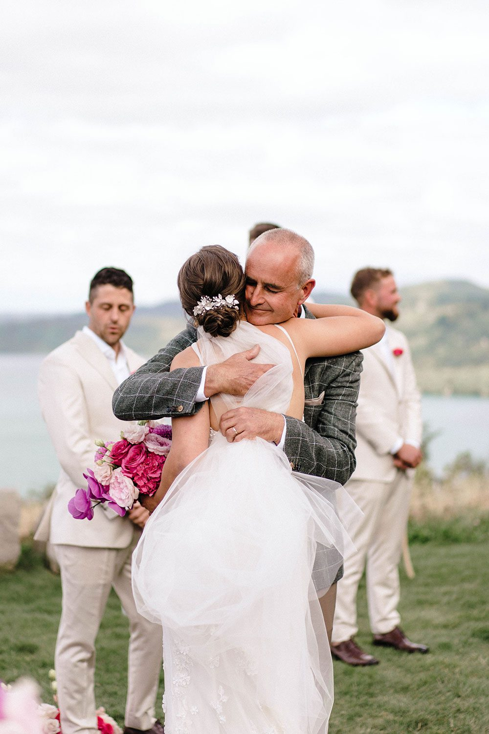 Bride wears bespoke E'More lace gown with boned bodice with hand beaded flower applique and full lace train by Auckland wedding dress maker Vinka designs - embrace with father at alter