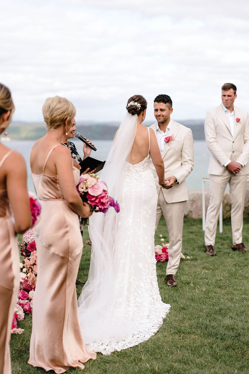 Bride wears bespoke E'More lace gown with boned bodice with hand beaded flower applique and full lace train by Auckland wedding dress maker Vinka designs - with groom at alter