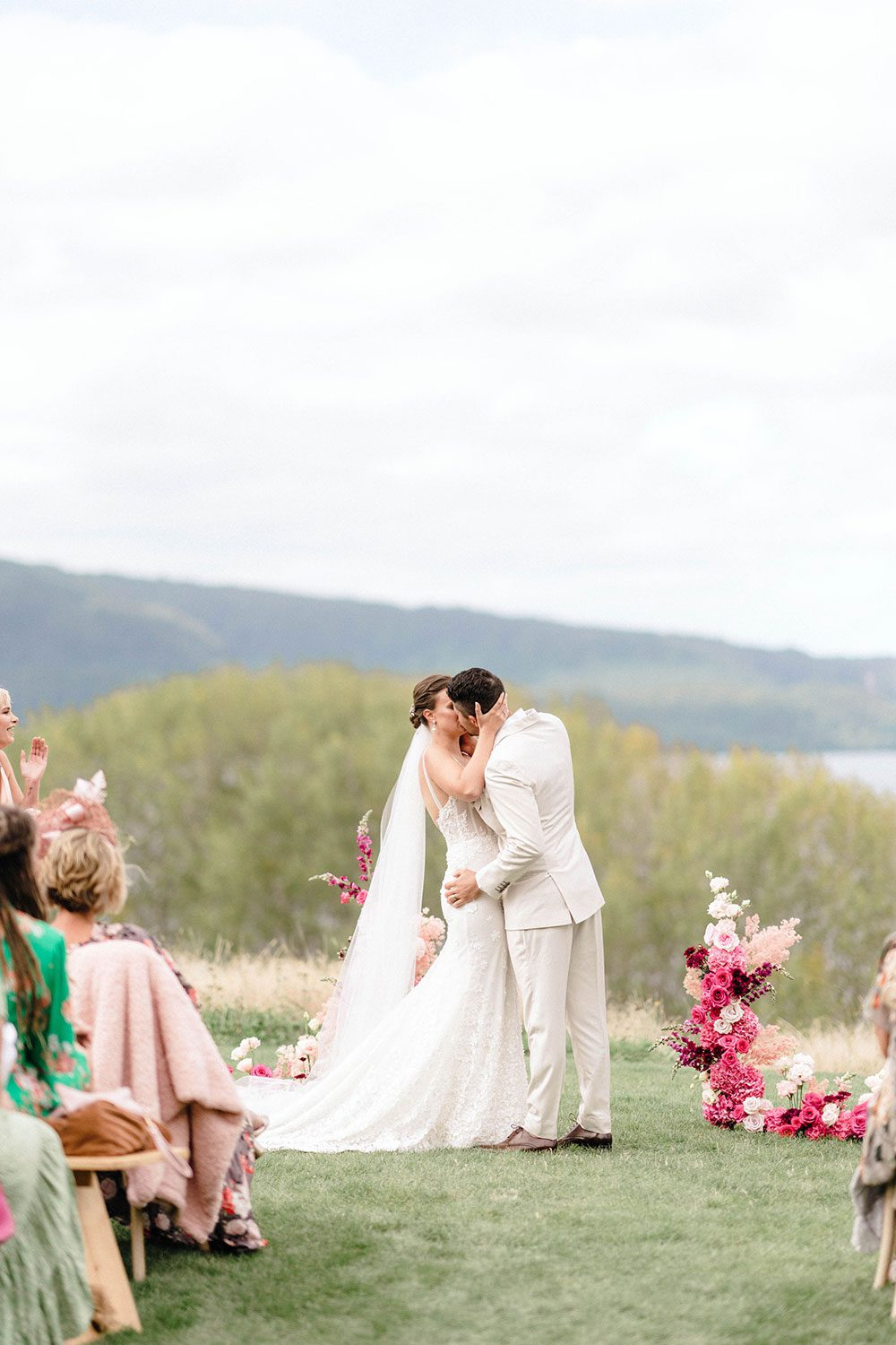 Bride wears bespoke E'More lace gown with boned bodice with hand beaded flower applique and full lace train by Auckland wedding dress maker Vinka designs - kissing groom at alter