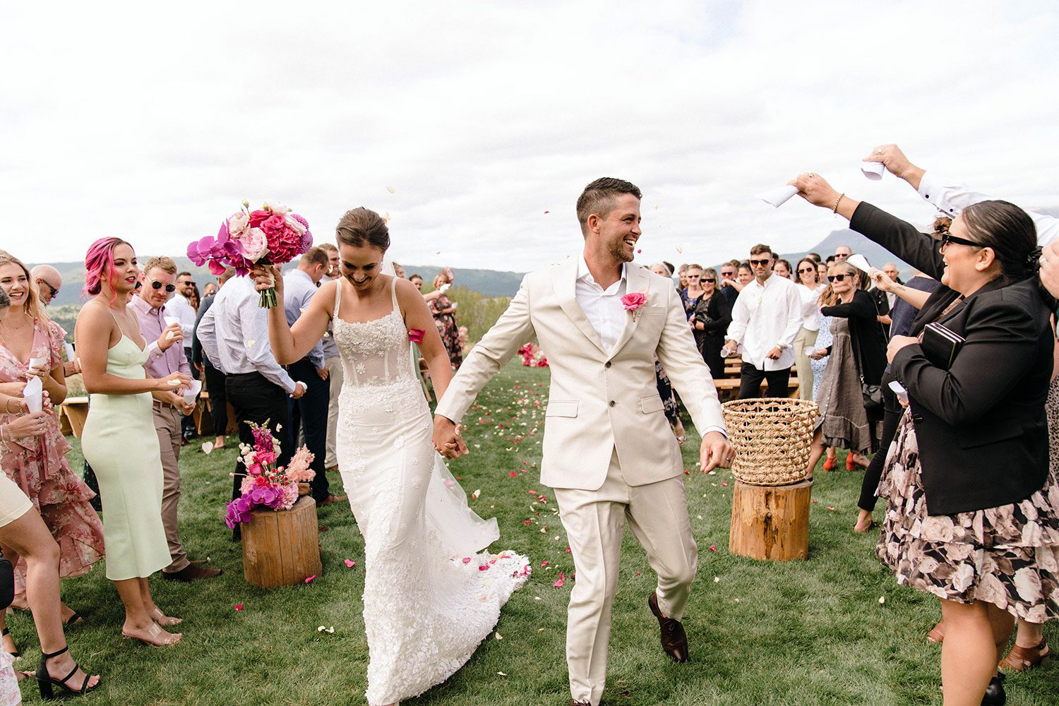 Bride wears bespoke E'More lace gown with boned bodice with hand beaded flower applique and full lace train by Auckland wedding dress maker Vinka designs - just married