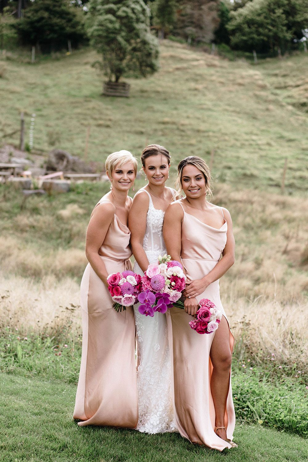 Bride wears bespoke E'More lace gown with boned bodice with hand beaded flower applique and full lace train by Auckland wedding dress maker Vinka designs - with bridesmaids and bouquets in field