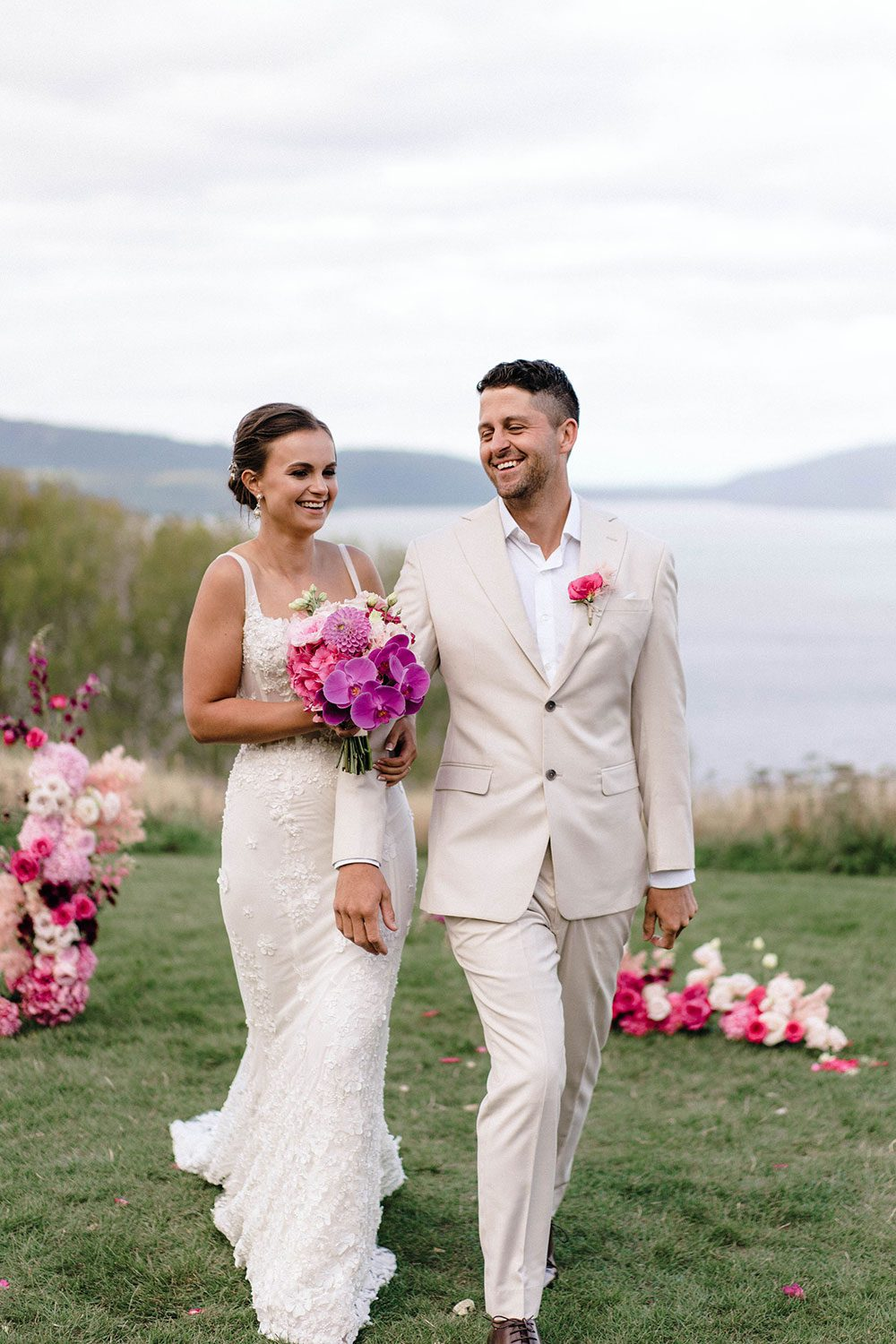 Bride wears bespoke E'More lace gown with boned bodice with hand beaded flower applique and full lace train by Auckland wedding dress maker Vinka designs - with groom holding bouquet