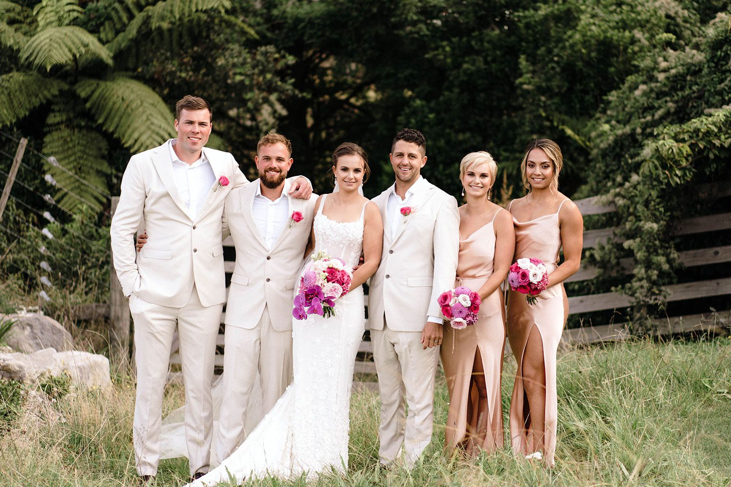 Bride wears bespoke E'More lace gown with boned bodice with hand beaded flower applique and full lace train by Auckland wedding dress maker Vinka designs - with bridesmaids and groomsmen in field