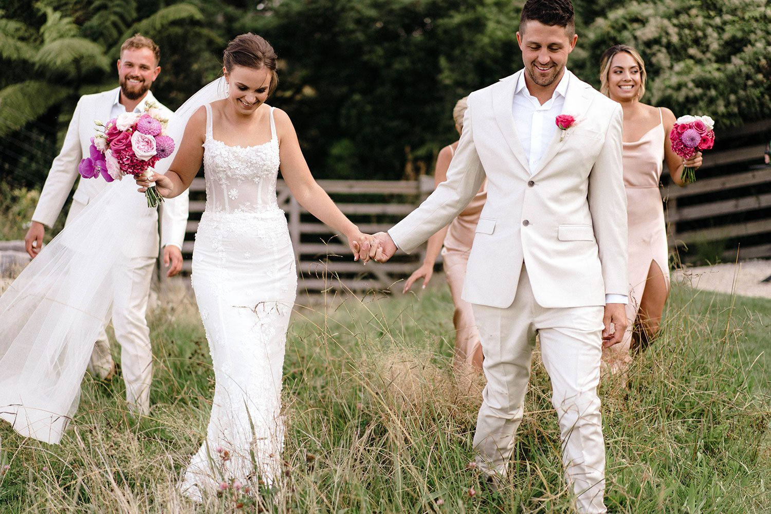 Bride wears bespoke E'More lace gown with boned bodice with hand beaded flower applique and full lace train by Auckland wedding dress maker Vinka designs - with groom and wedding party walking in field