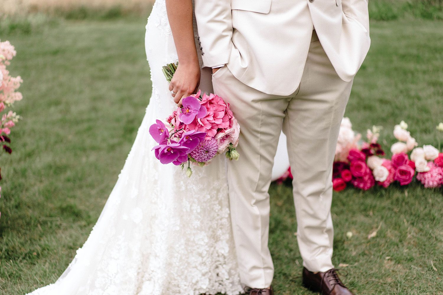 Bride wears bespoke E'More lace gown with boned bodice with hand beaded flower applique and full lace train by Auckland wedding dress maker Vinka designs - half shot with groom and bouquet