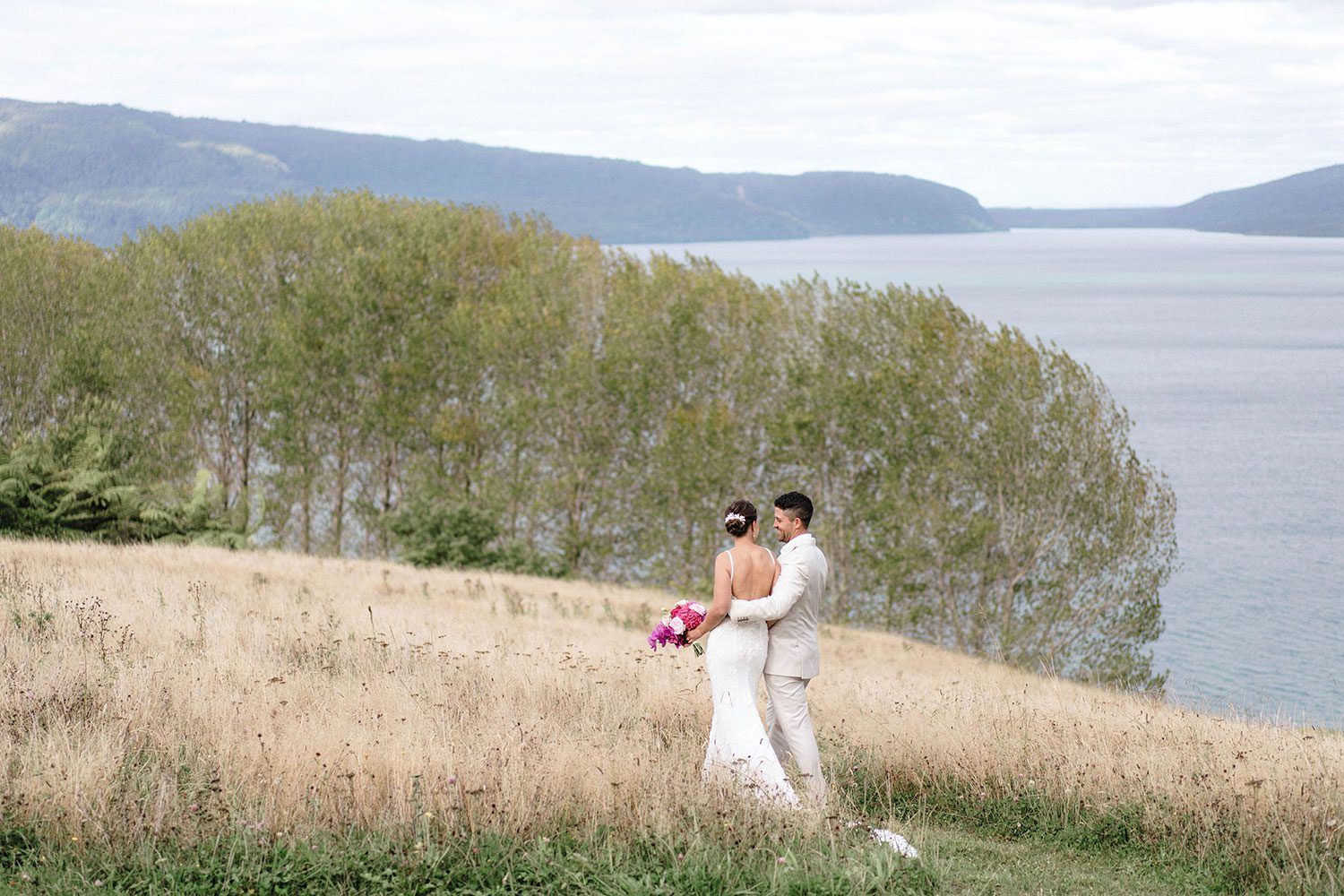 Bride wears bespoke E'More lace gown with boned bodice with hand beaded flower applique and full lace train by Auckland wedding dress maker Vinka designs - with groom back embrace walking in field