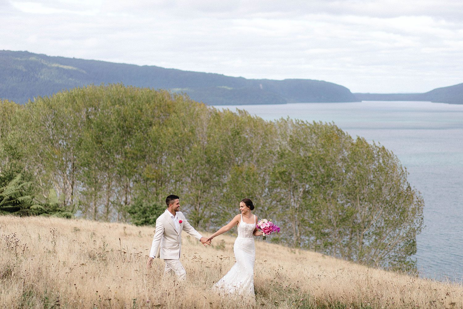 Bride wears bespoke E'More lace gown with boned bodice with hand beaded flower applique and full lace train by Auckland wedding dress maker Vinka designs - with groom holding hands walking in field