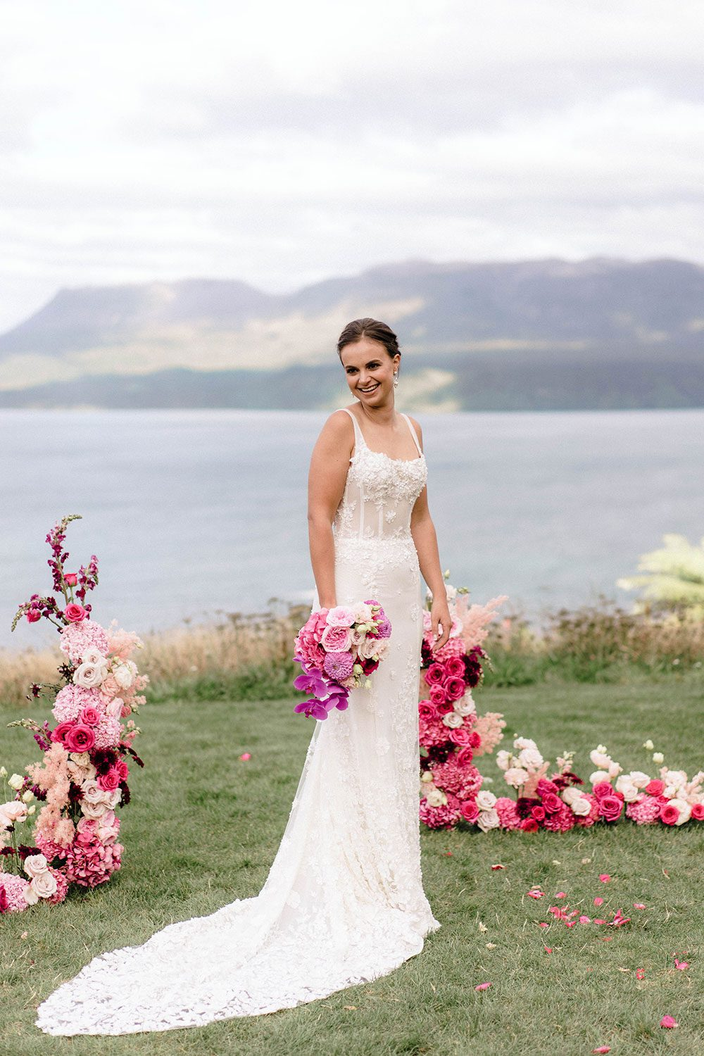 Bride wears bespoke E'More lace gown with boned bodice with hand beaded flower applique and full lace train by Auckland wedding dress maker Vinka designs - holding bouquet at alter