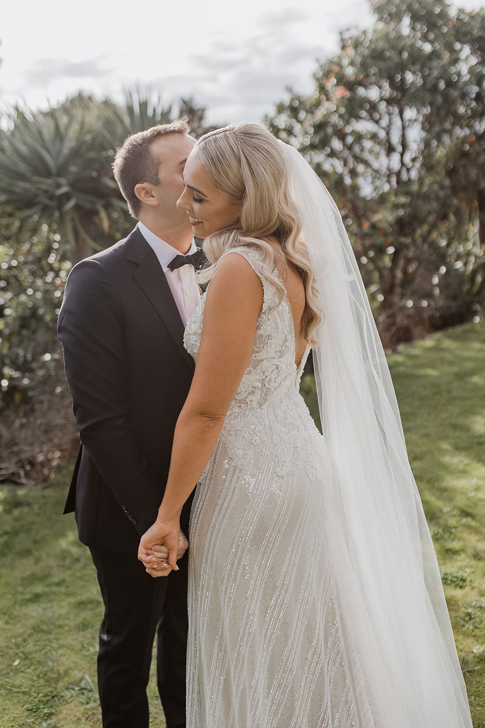 Bride wearing bespoke fitted V-neck gown in beaded lace with front split and sheer beaded overlay by Vinka bridal boutique NZ- with groom in garden kissing on cheek