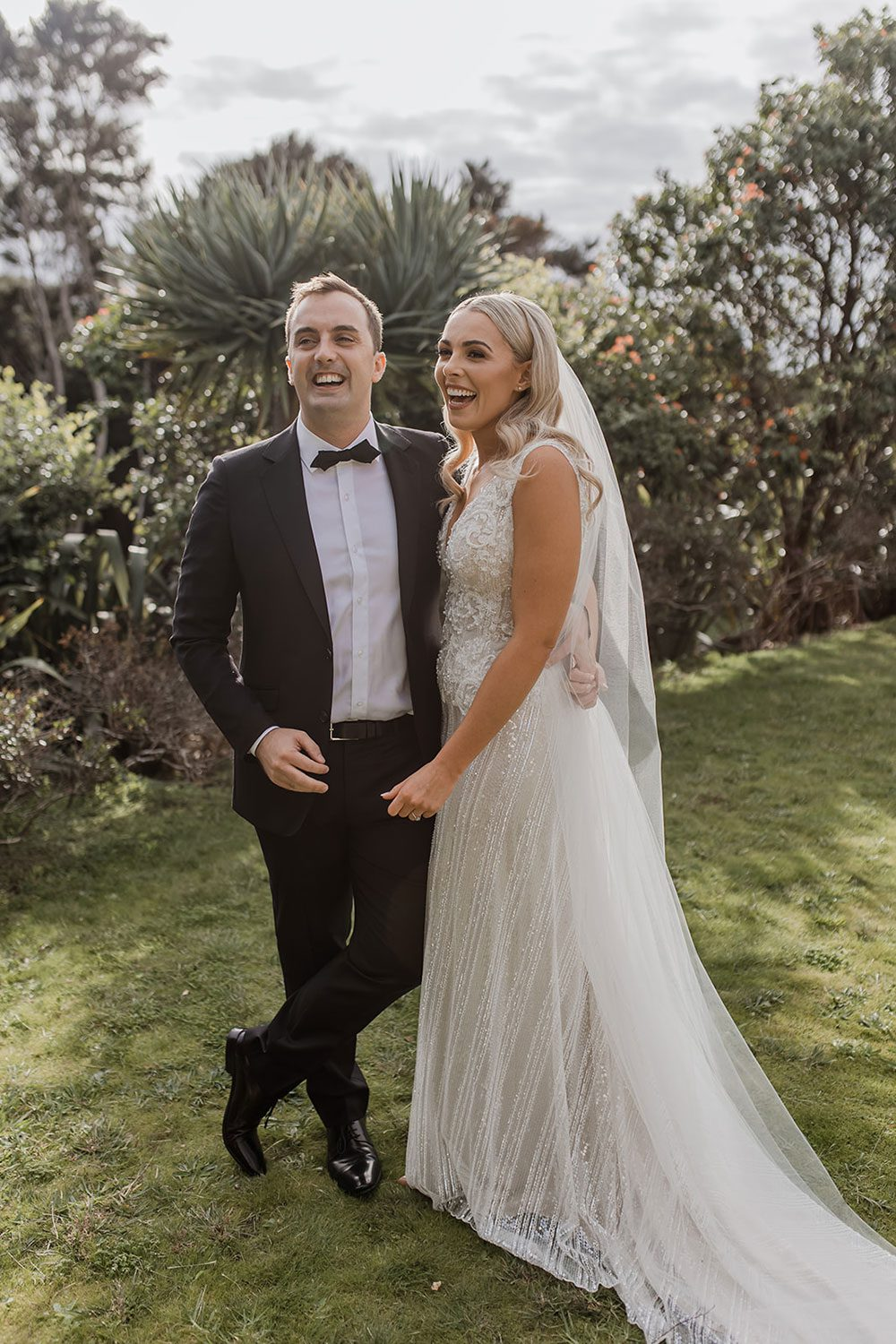 Bride wearing bespoke fitted V-neck gown in beaded lace with front split and sheer beaded overlay by Vinka bridal boutique NZ- with groom in garden laughing