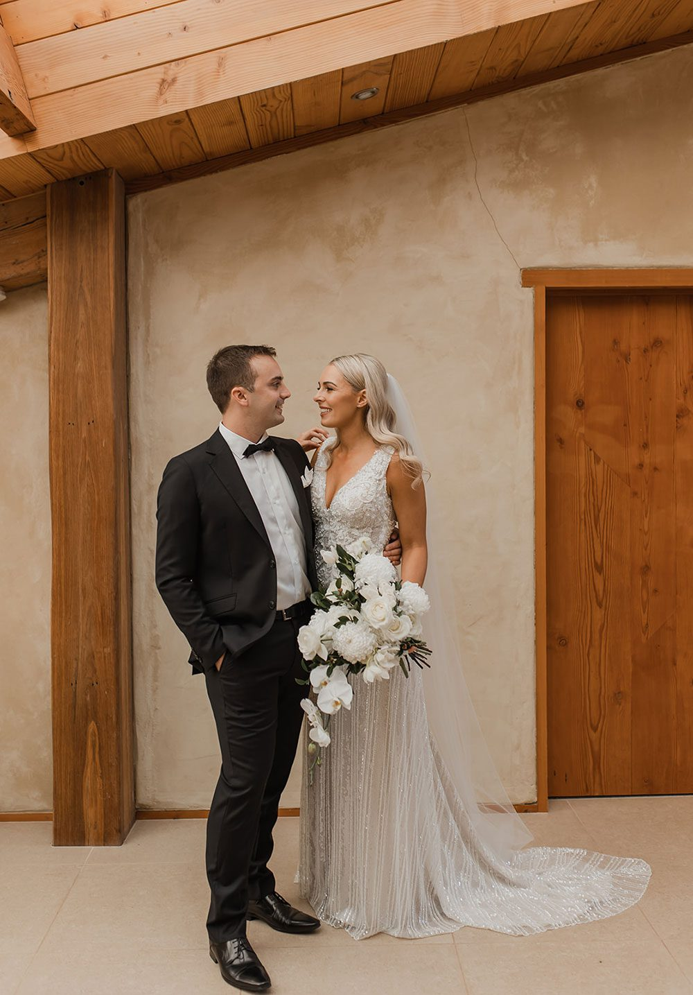 Bride wearing bespoke fitted V-neck gown in beaded lace with front split and sheer beaded overlay by Vinka bridal boutique NZ- with groom in front of wall