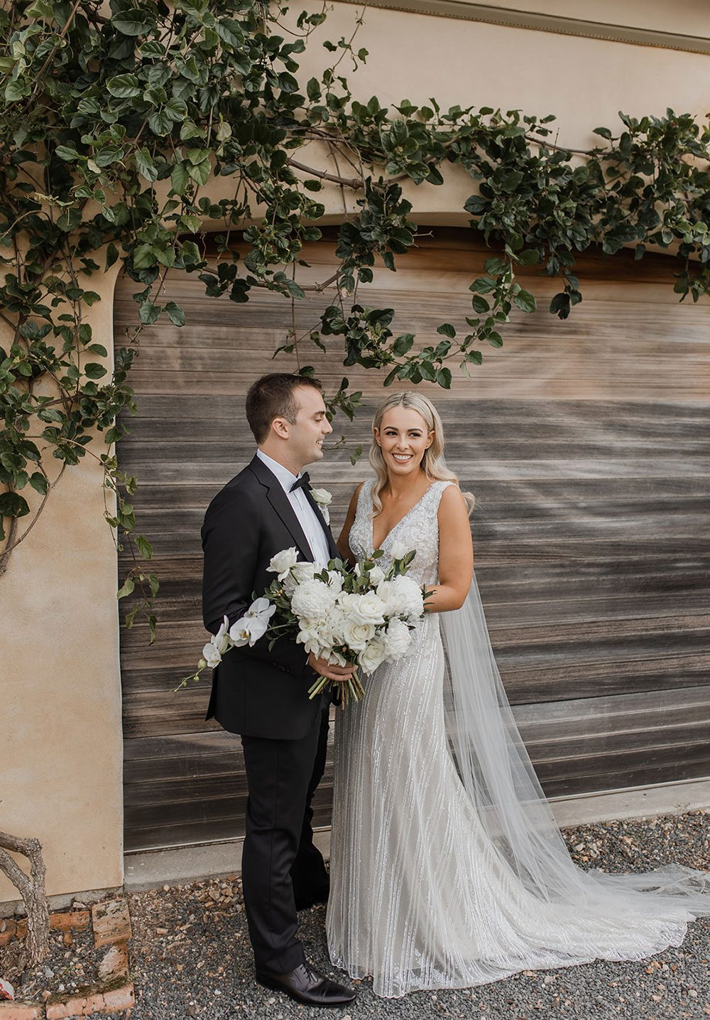 Bride wearing bespoke fitted V-neck gown in beaded lace with front split and sheer beaded overlay by Vinka bridal boutique NZ- with groom