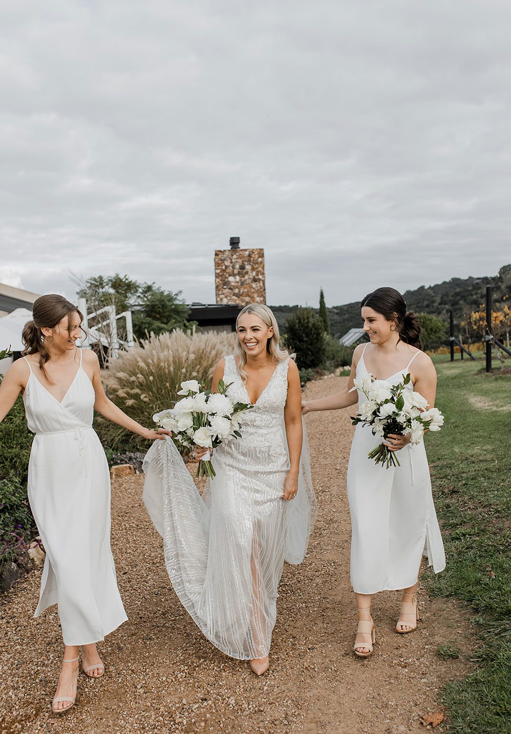 Bride wearing bespoke fitted V-neck gown in beaded lace with front split and sheer beaded overlay by Vinka bridal boutique NZ- walking with bridesmaids holding dress