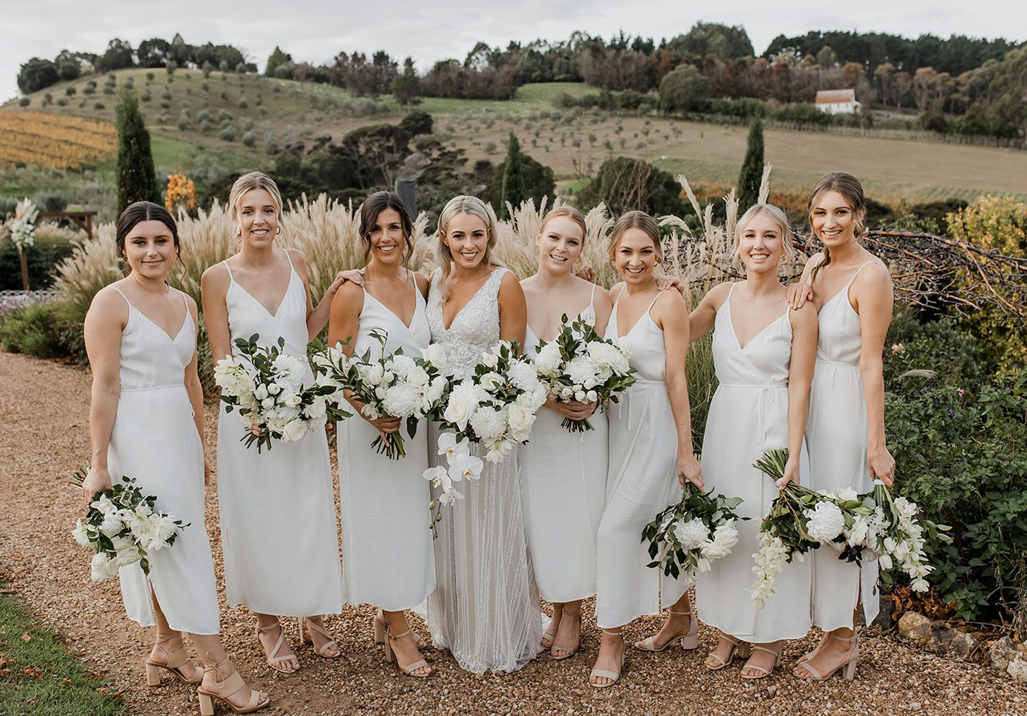 Bride wearing bespoke fitted V-neck gown in beaded lace with front split and sheer beaded overlay by Vinka bridal boutique NZ- with bridesmaids with view behind