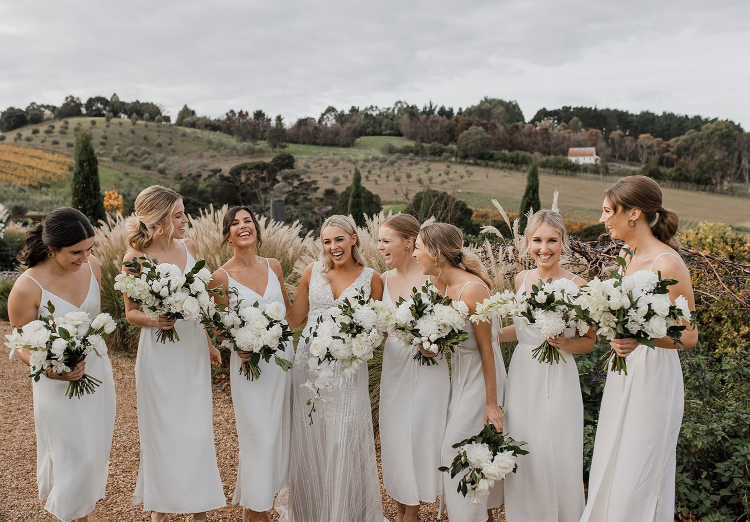 Bride wearing bespoke fitted V-neck gown in beaded lace with front split and sheer beaded overlay by Vinka bridal boutique NZ- laughing with bridesmaids with view behind