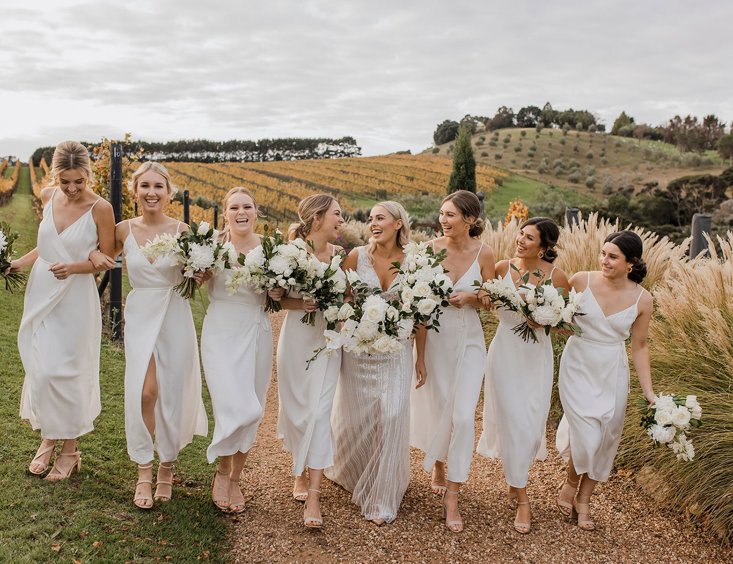 Bride wearing bespoke fitted V-neck gown in beaded lace with front split and sheer beaded overlay by Vinka bridal boutique NZ- laughing with bridesmaids view behind