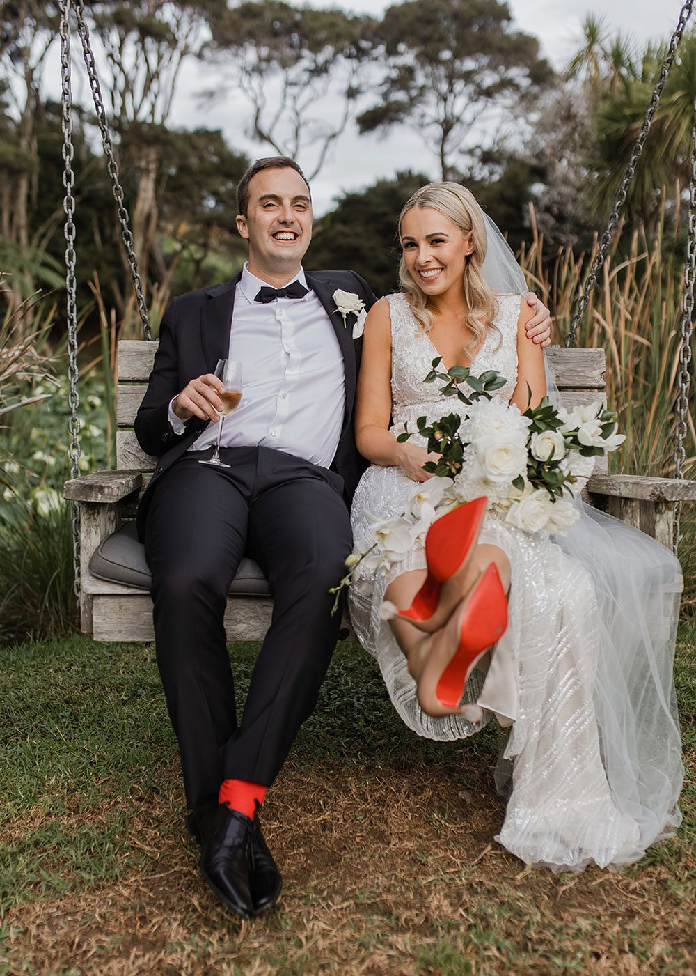 Bride wearing bespoke fitted V-neck gown in beaded lace with front split and sheer beaded overlay by Vinka bridal boutique NZ- sitting on chair with groom