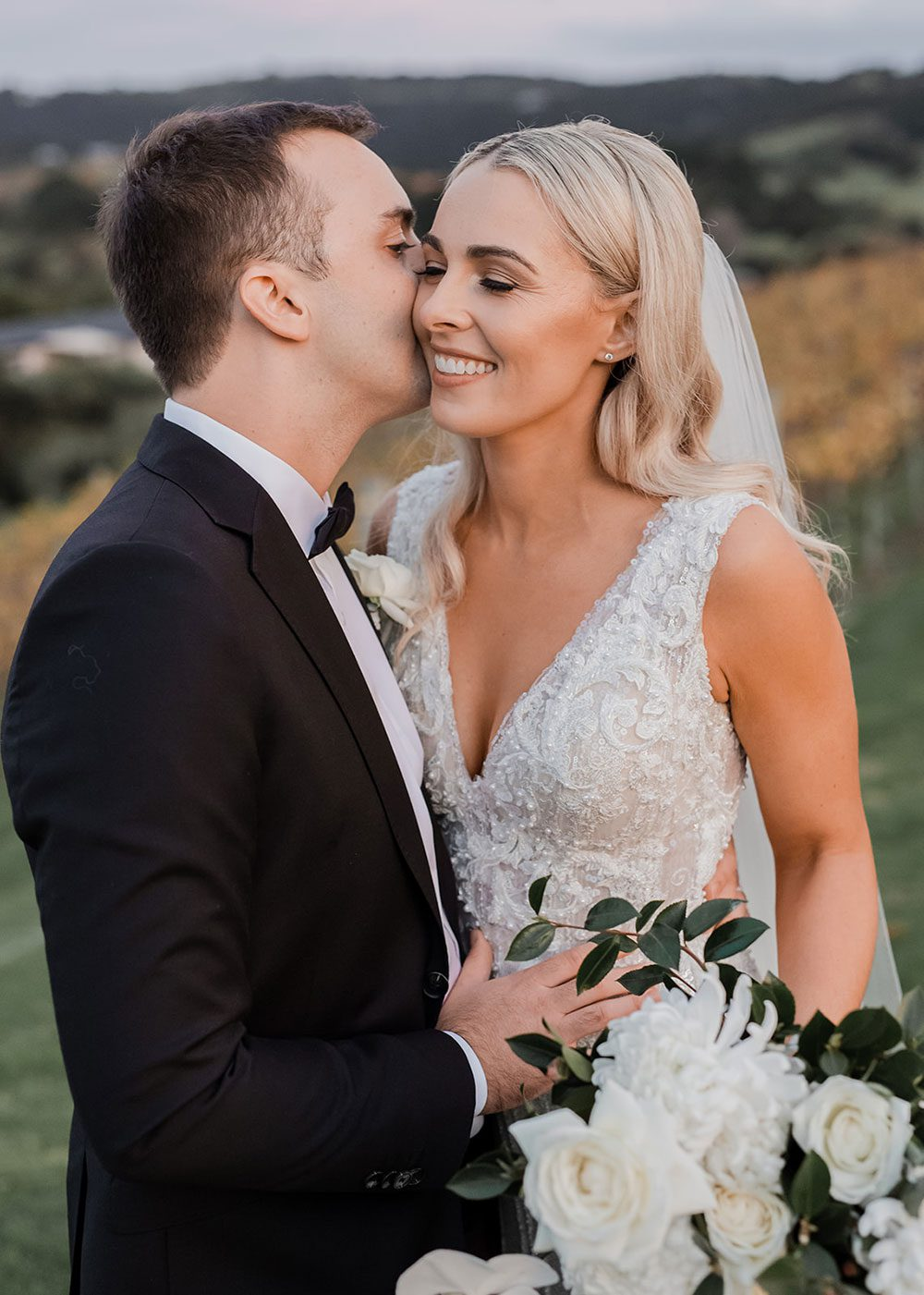 Bride wearing bespoke fitted V-neck gown in beaded lace with front split and sheer beaded overlay by Vinka bridal boutique NZ- close up groom kissing bride on cheek