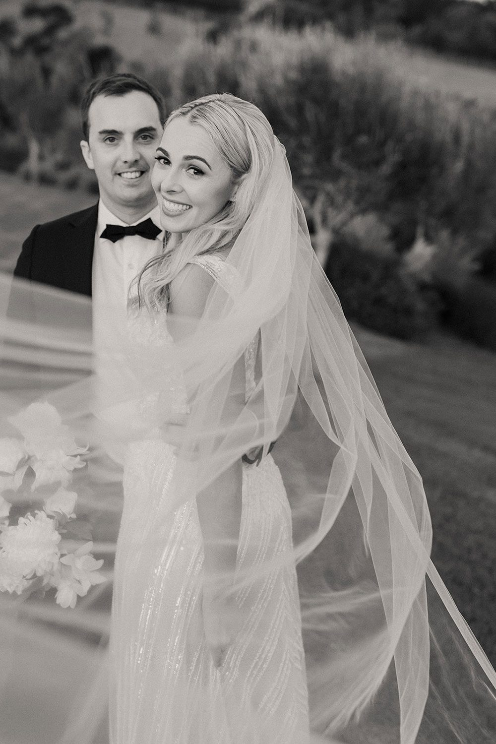 Bride wearing bespoke fitted V-neck gown in beaded lace with front split and sheer beaded overlay by Vinka bridal boutique NZ- black and white with groom near car