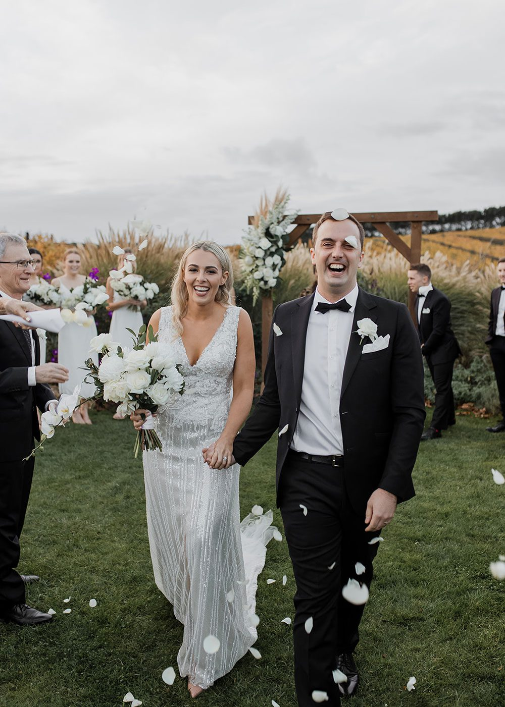 Bride wearing bespoke fitted V-neck gown in beaded lace with front split and sheer beaded overlay by Vinka bridal boutique NZ- just married