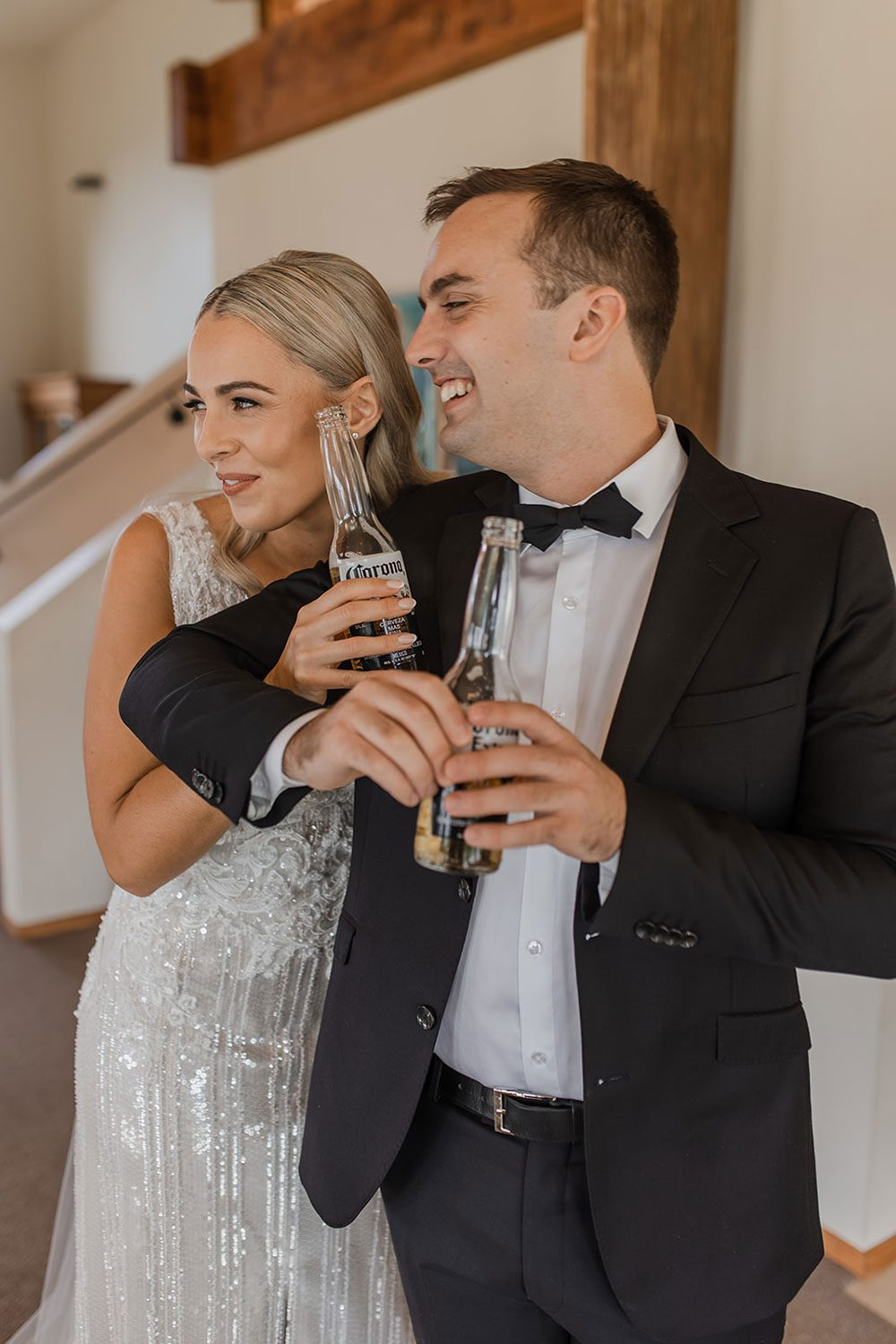 Bride wearing bespoke fitted V-neck gown in beaded lace with front split and sheer beaded overlay by Vinka bridal boutique NZ- having a drink with groom