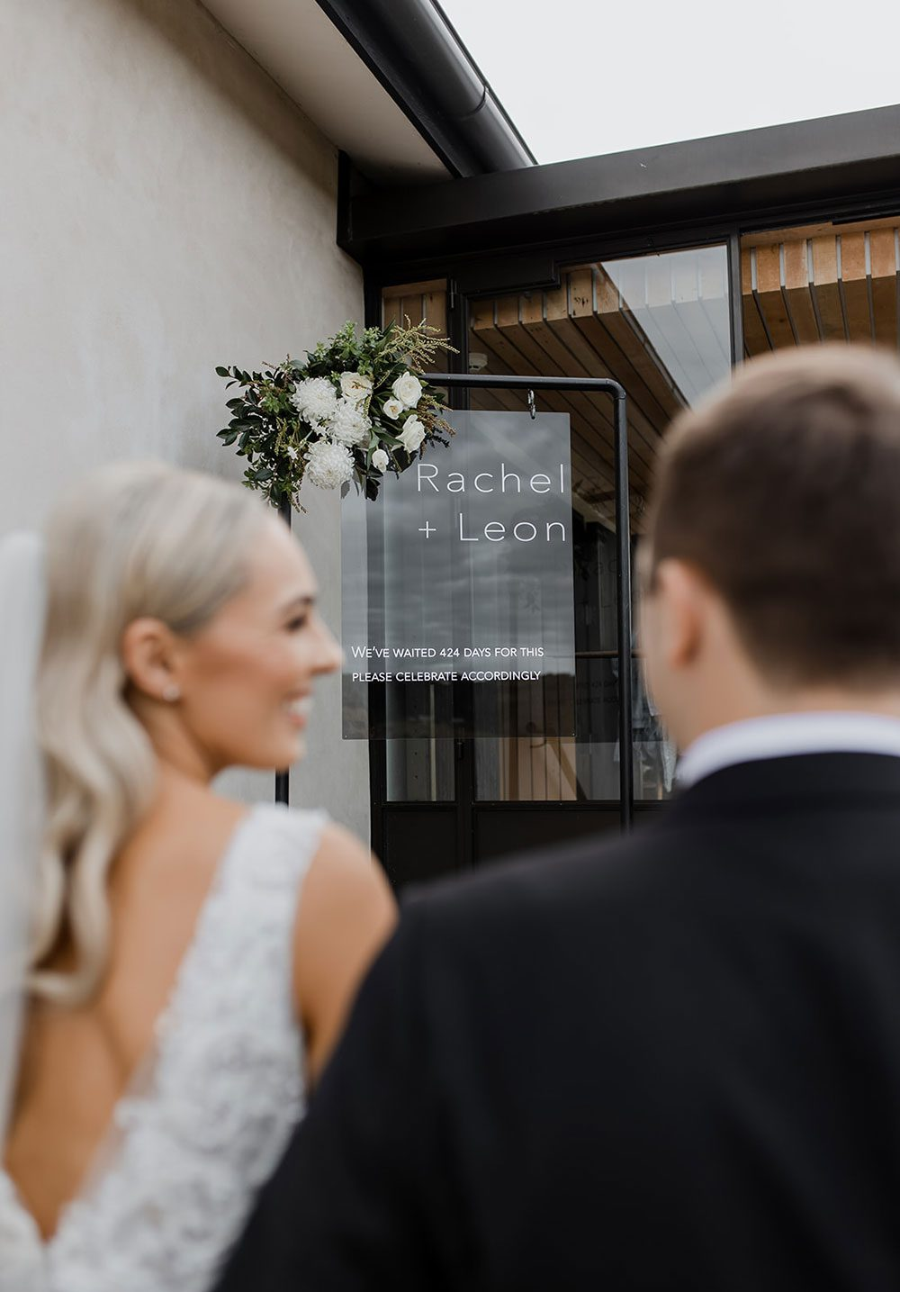 Bride wearing bespoke fitted V-neck gown in beaded lace with front split and sheer beaded overlay by Vinka bridal boutique NZ- waking in to recception