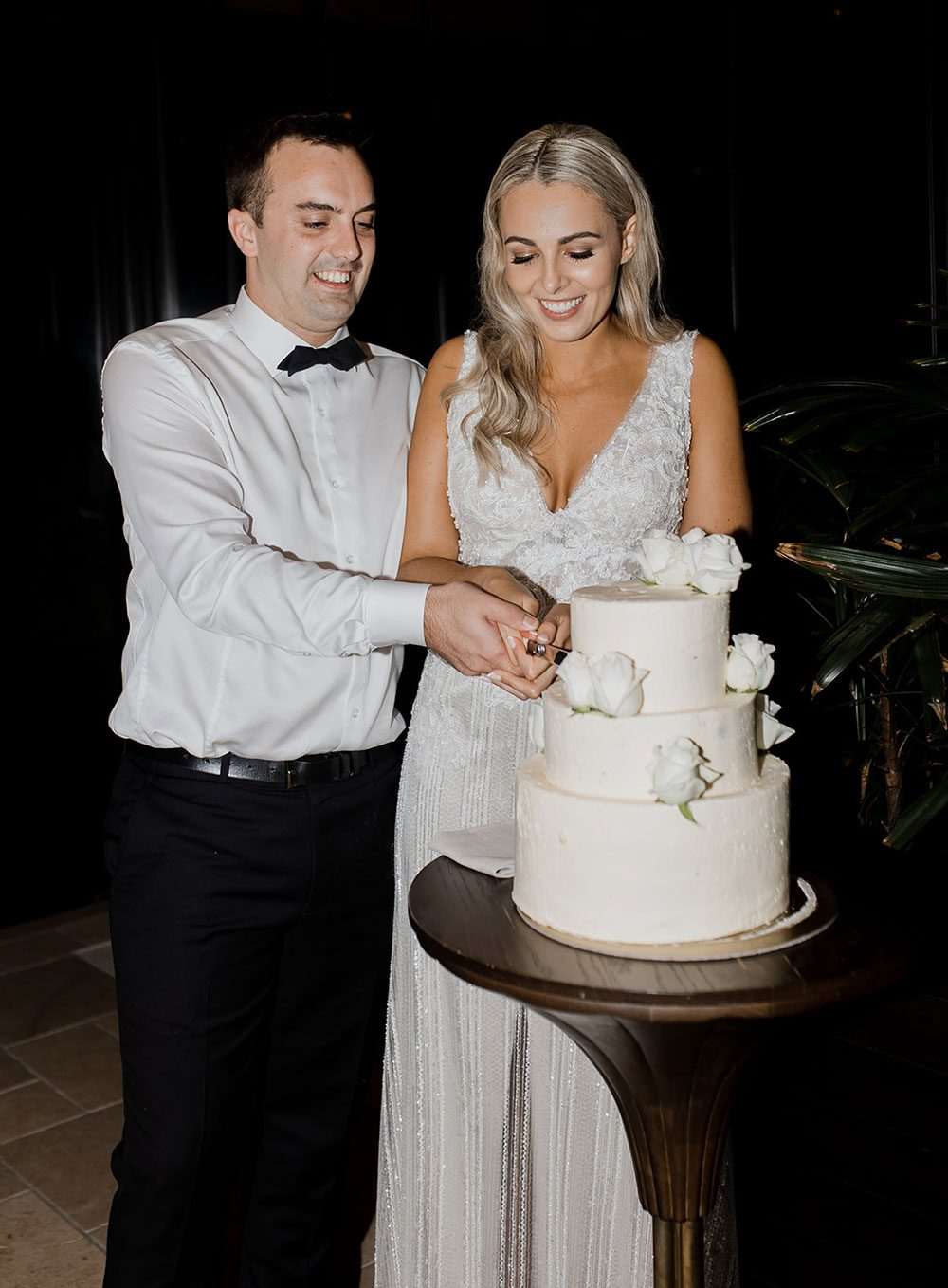 Bride wearing bespoke fitted V-neck gown in beaded lace with front split and sheer beaded overlay by Vinka bridal boutique NZ- cutting cake