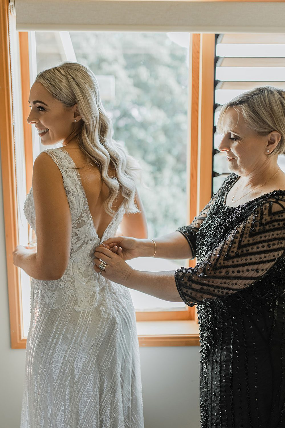 Bride wearing bespoke fitted V-neck gown in beaded lace with front split and sheer beaded overlay by VInka Bridal boutique- getting dressed