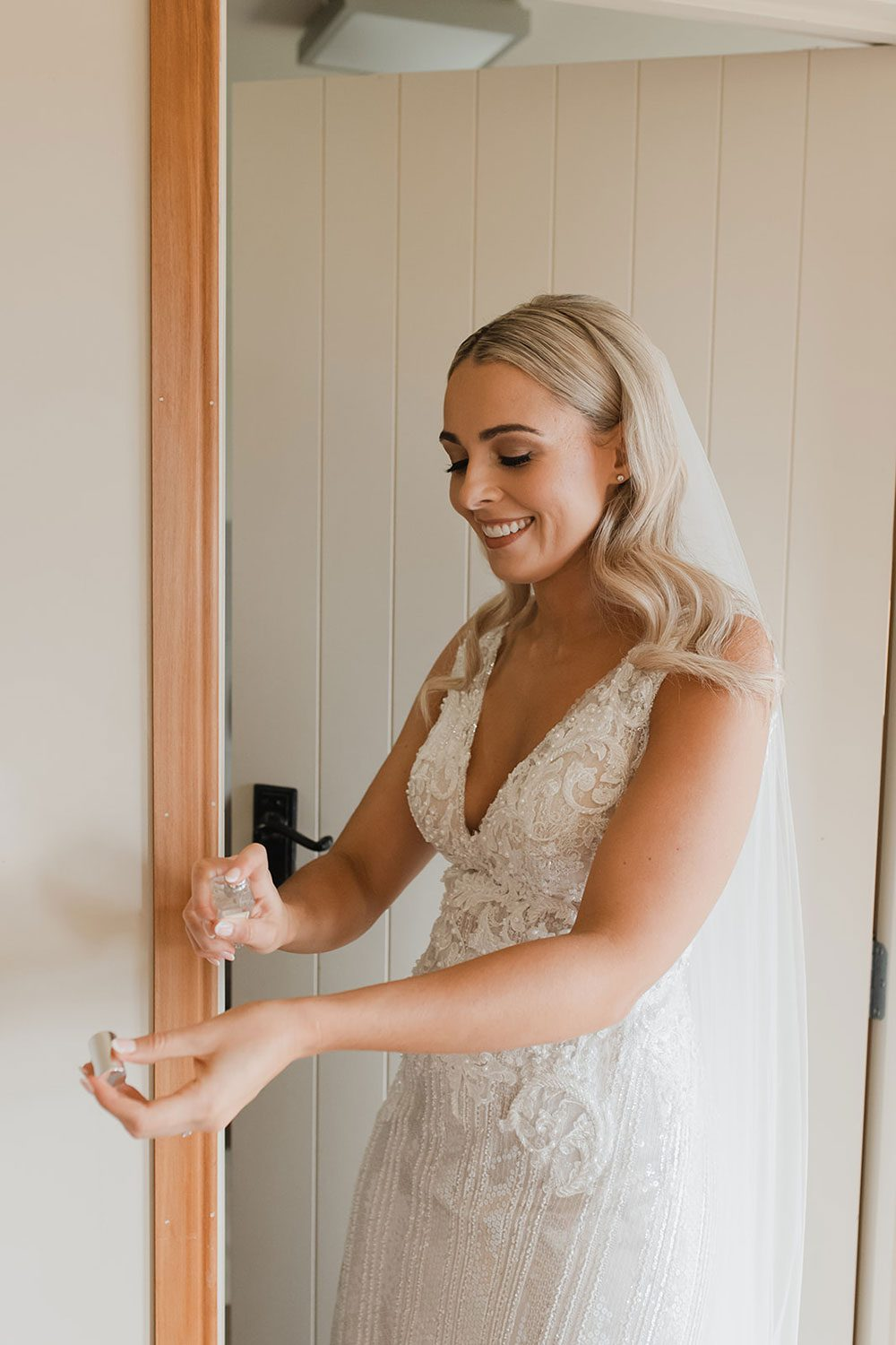 Bride wearing bespoke fitted V-neck gown in beaded lace with front split and sheer overlay by Vinka bridal boutique NZ - putting on perfume -neck gown in beaded lace with front split and sheer beaded overlay - putting on perfume
