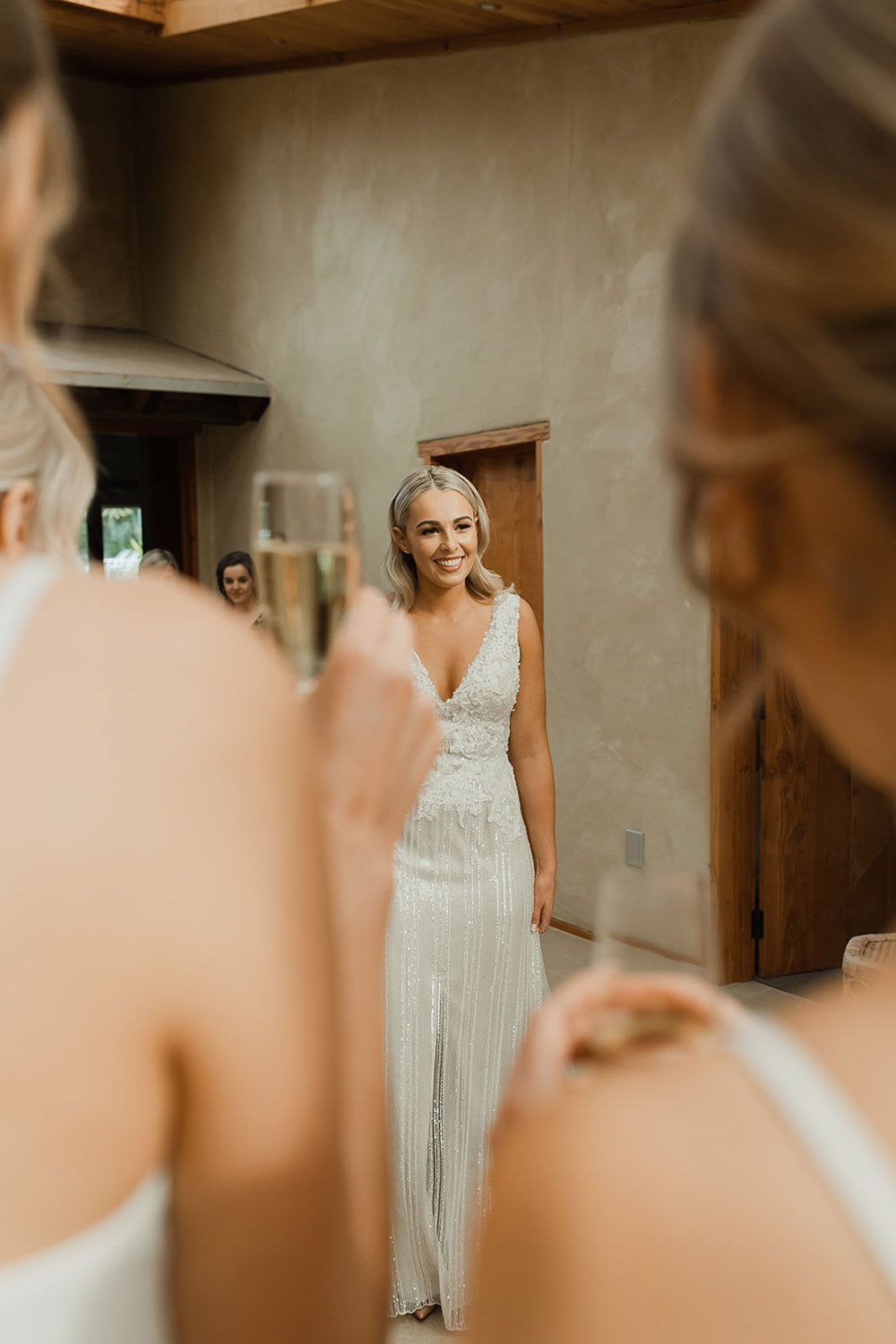 Bride wearing bespoke fitted V-neck gown in beaded lace with front split and sheer overlay by Vinka bridal boutique NZ - just ready