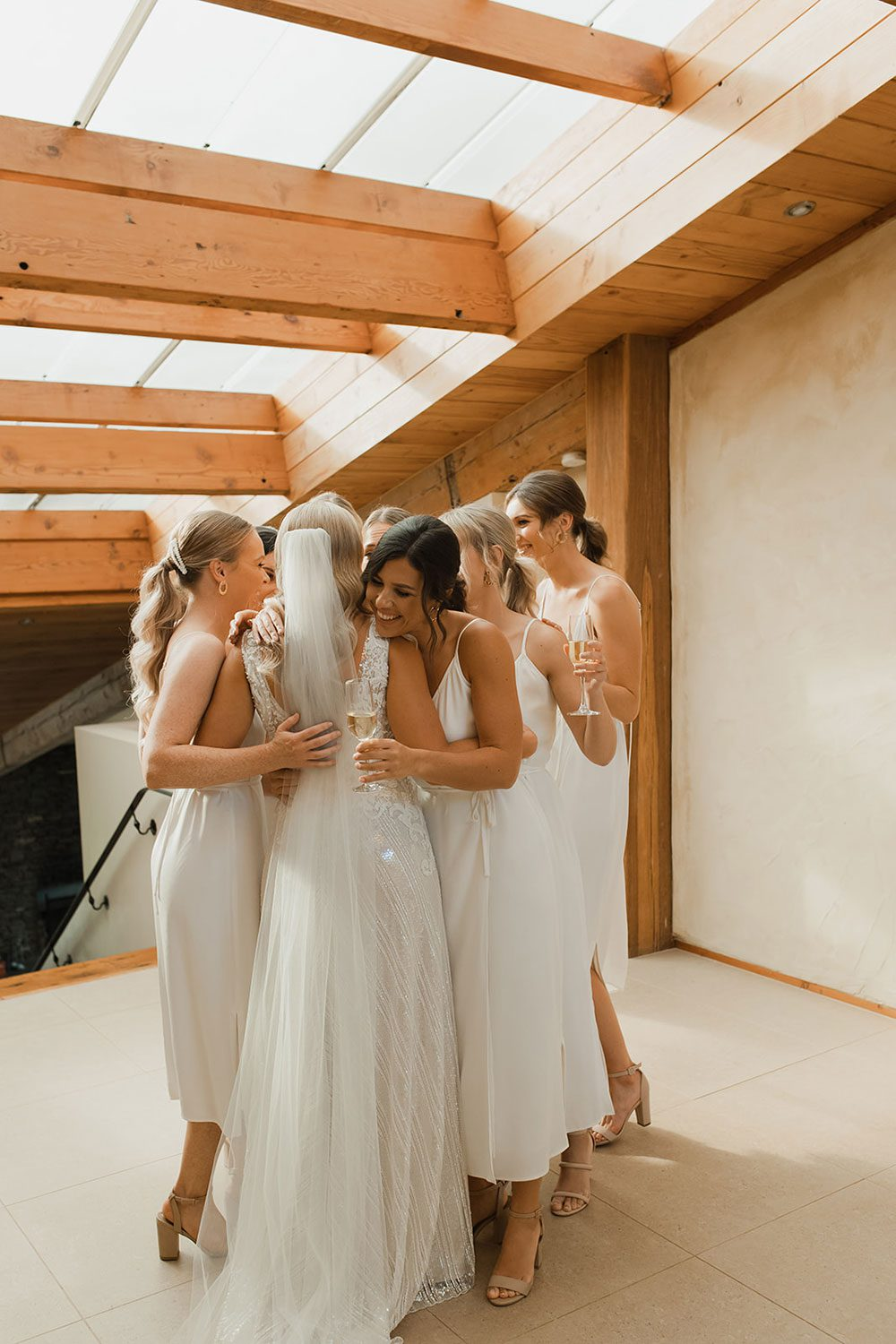 Bride wearing bespoke fitted V-neck gown in beaded lace with front split and sheer beaded overlay by Vinka bridal boutique NZ- hugging bridesmaids