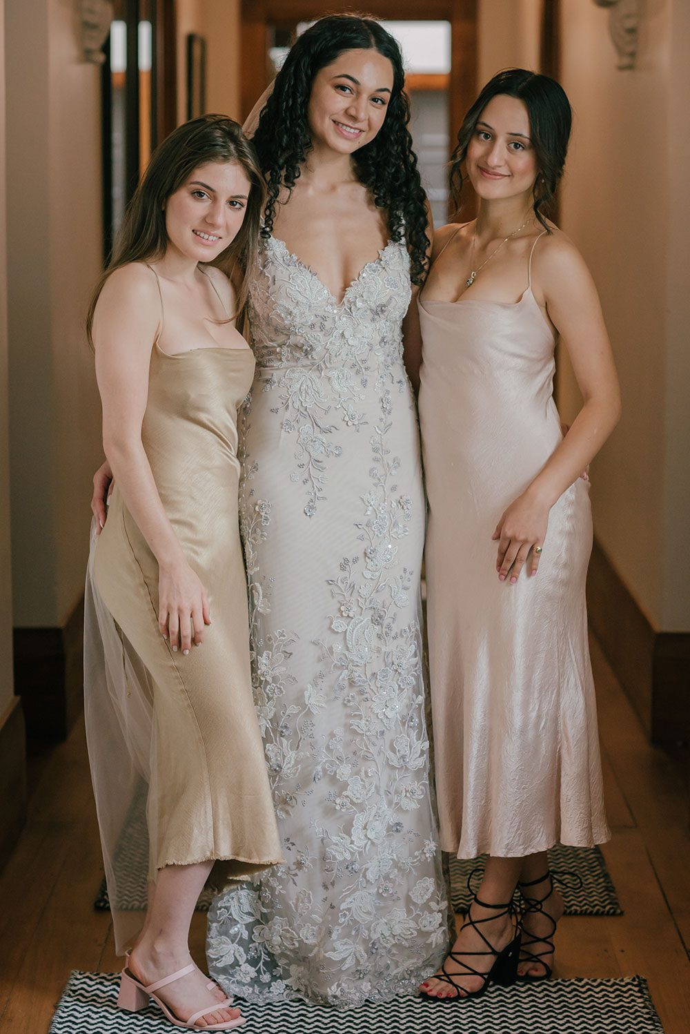 Bride wearing Kazumi Gown in soft grey with hand embellished lace and a low back - with bridesmaids in hall