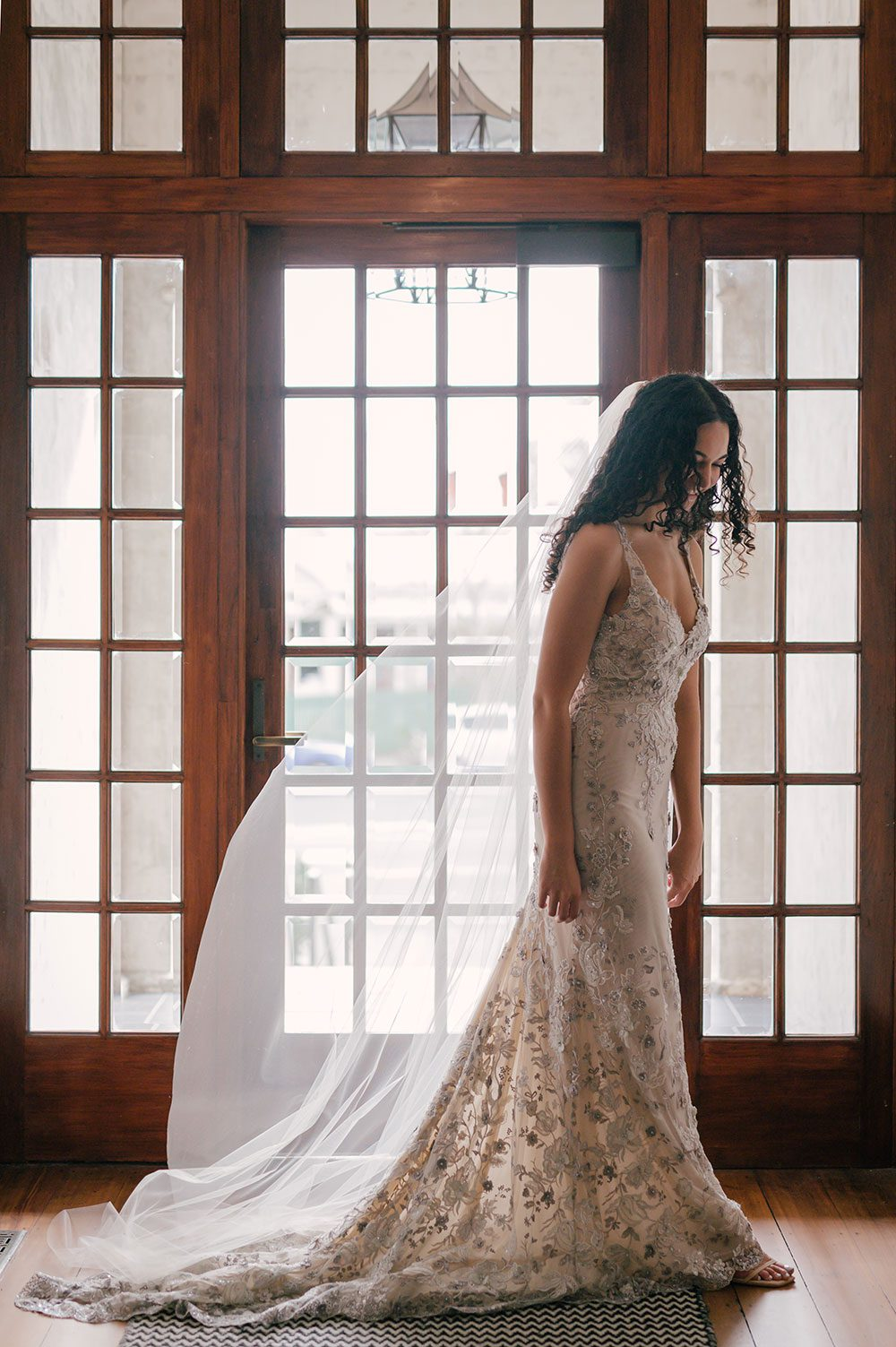 Bride wearing Kazumi Gown in soft grey with hand embellished lace and a low back - in front of window