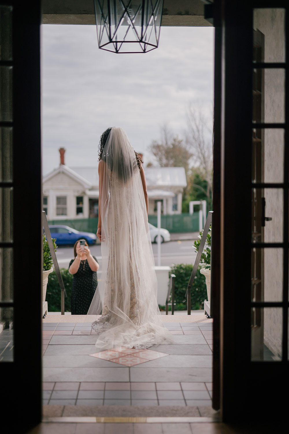 Bride wearing Kazumi Gown in soft grey with hand embellished lace and a low back - in doorway outside