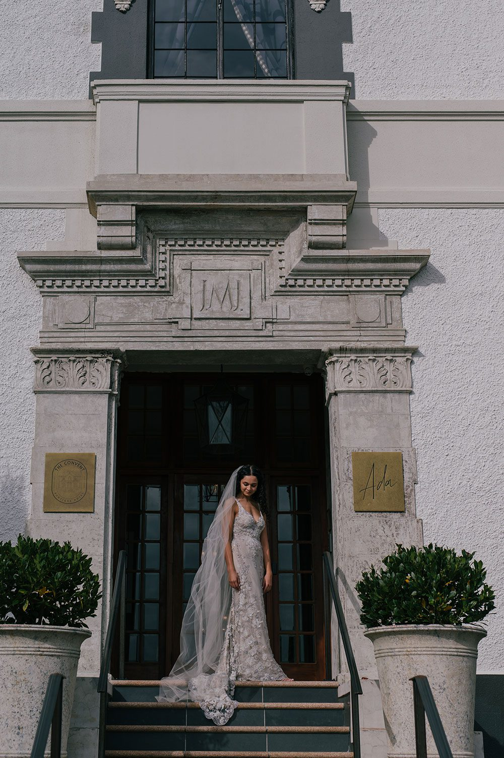 Bride wearing Kazumi Gown in soft grey with hand embellished lace and a low back - in doorway at top of stairs