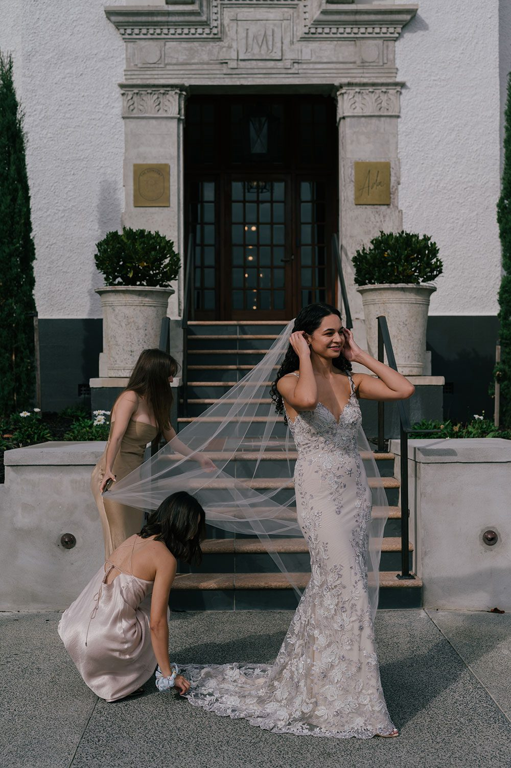 Bride wearing Kazumi Gown in soft grey with hand embellished lace and a low back - at bottom of stairs with bridesmaids holding veil