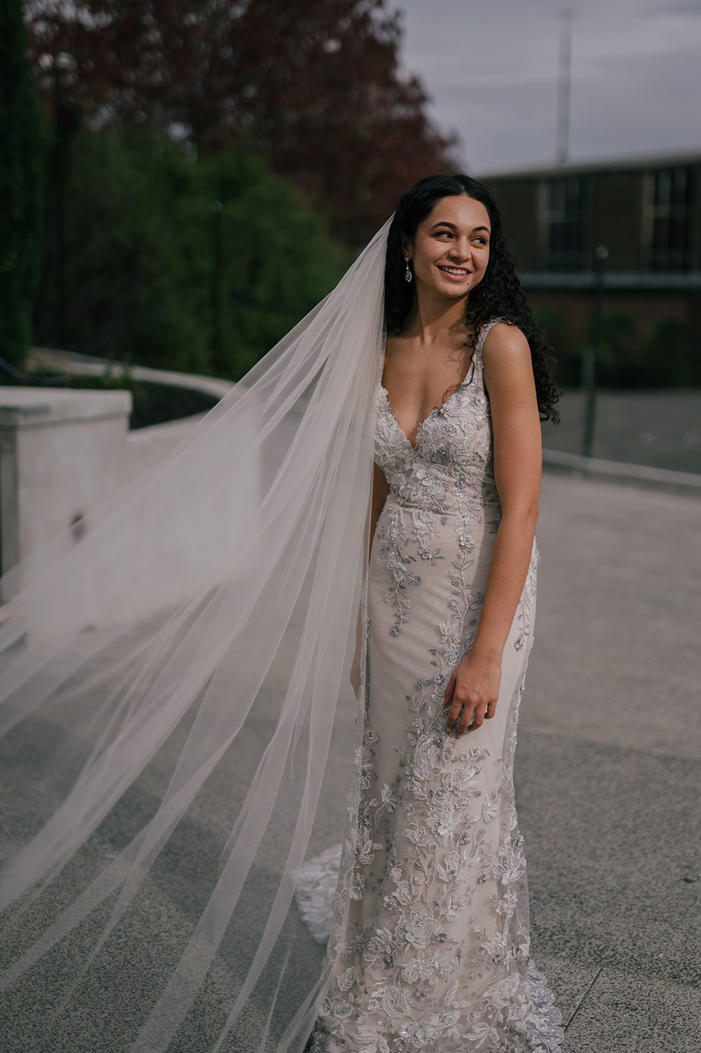 Bride wearing Kazumi Gown in soft grey with hand embellished lace and a low back - outside veil in wind