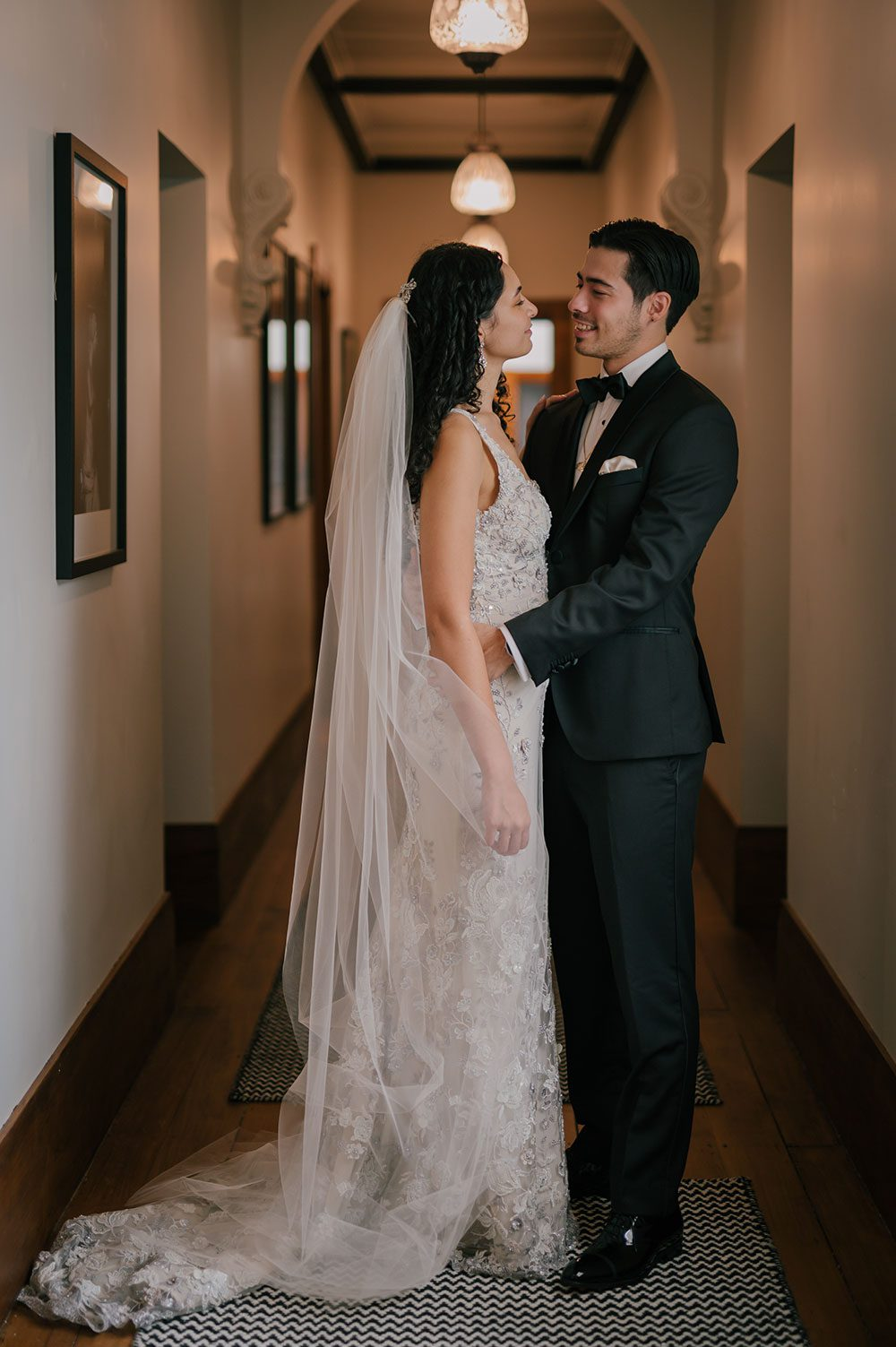 Bride wearing Kazumi Gown in soft grey with hand embellished lace and a low back - with groom in hallway