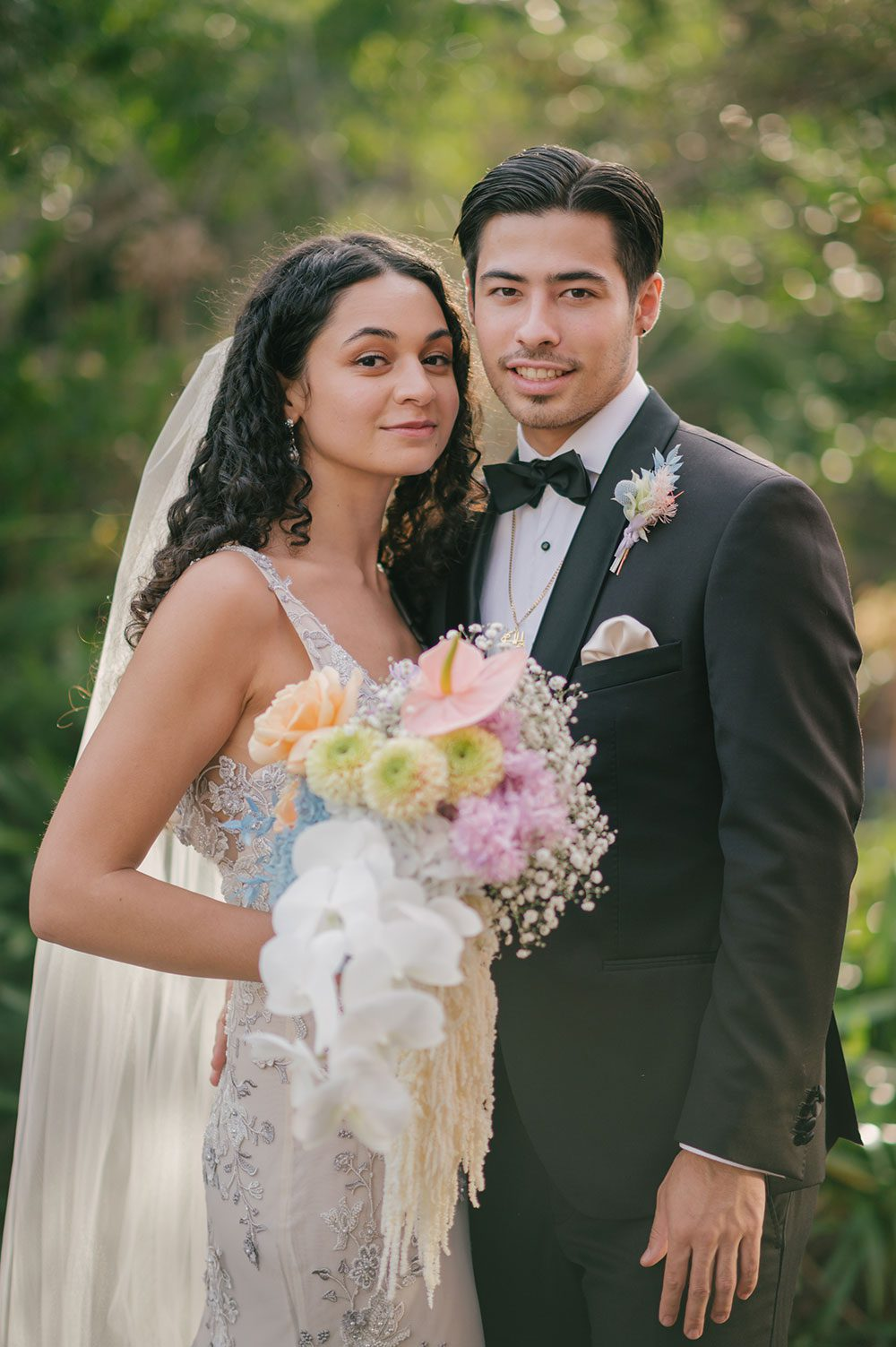 Bride wearing Kazumi Gown in soft grey with hand embellished lace and a low back - outside with groom