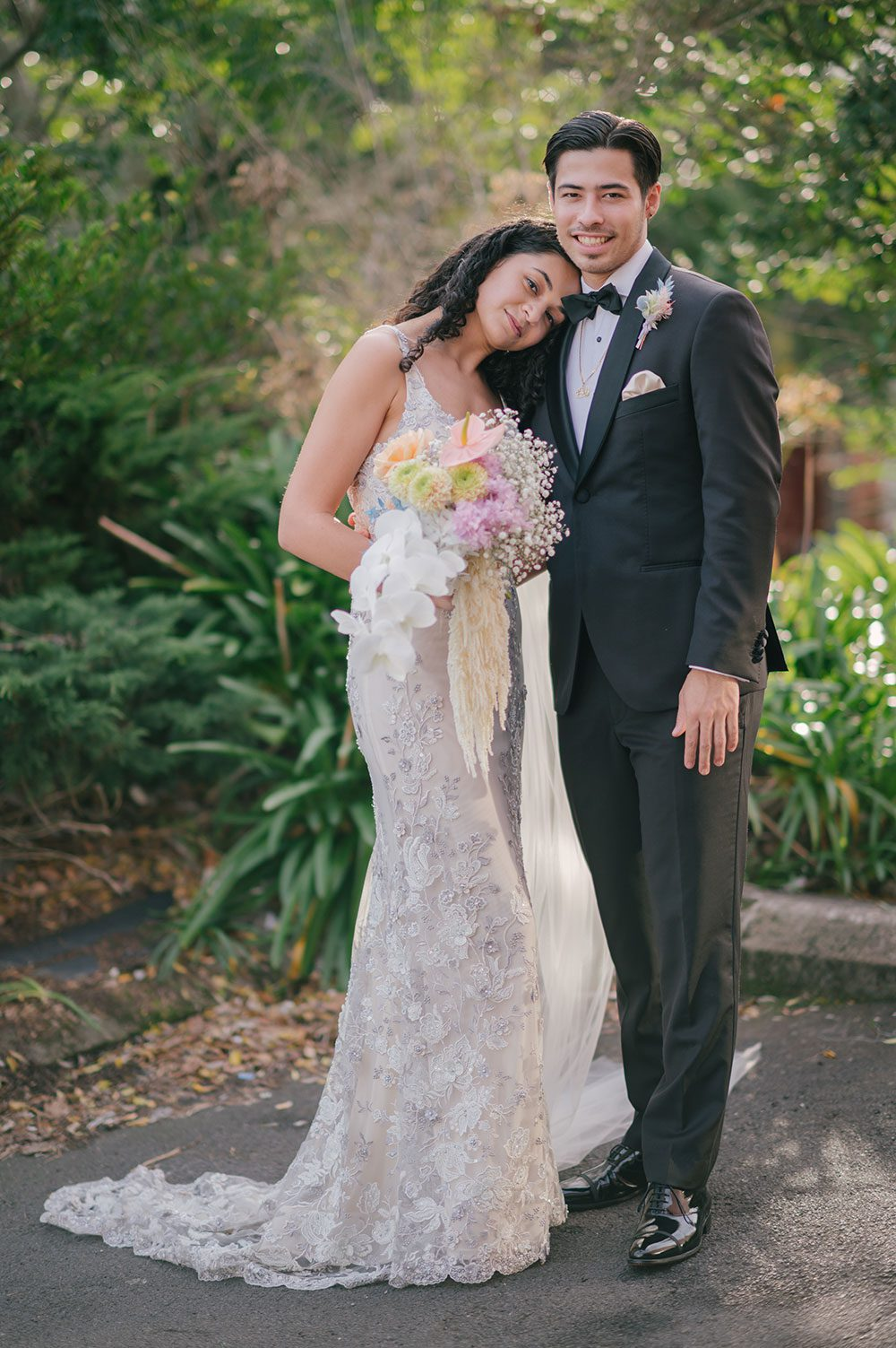 Bride wearing Kazumi Gown in soft grey with hand embellished lace and a low back - outside with groom holding bouquet full length