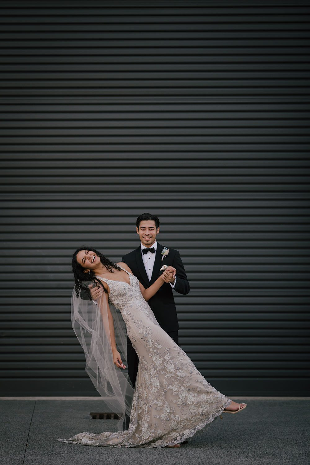 Bride wearing Kazumi Gown in soft grey with hand embellished lace and a low back - dancing outside with groom