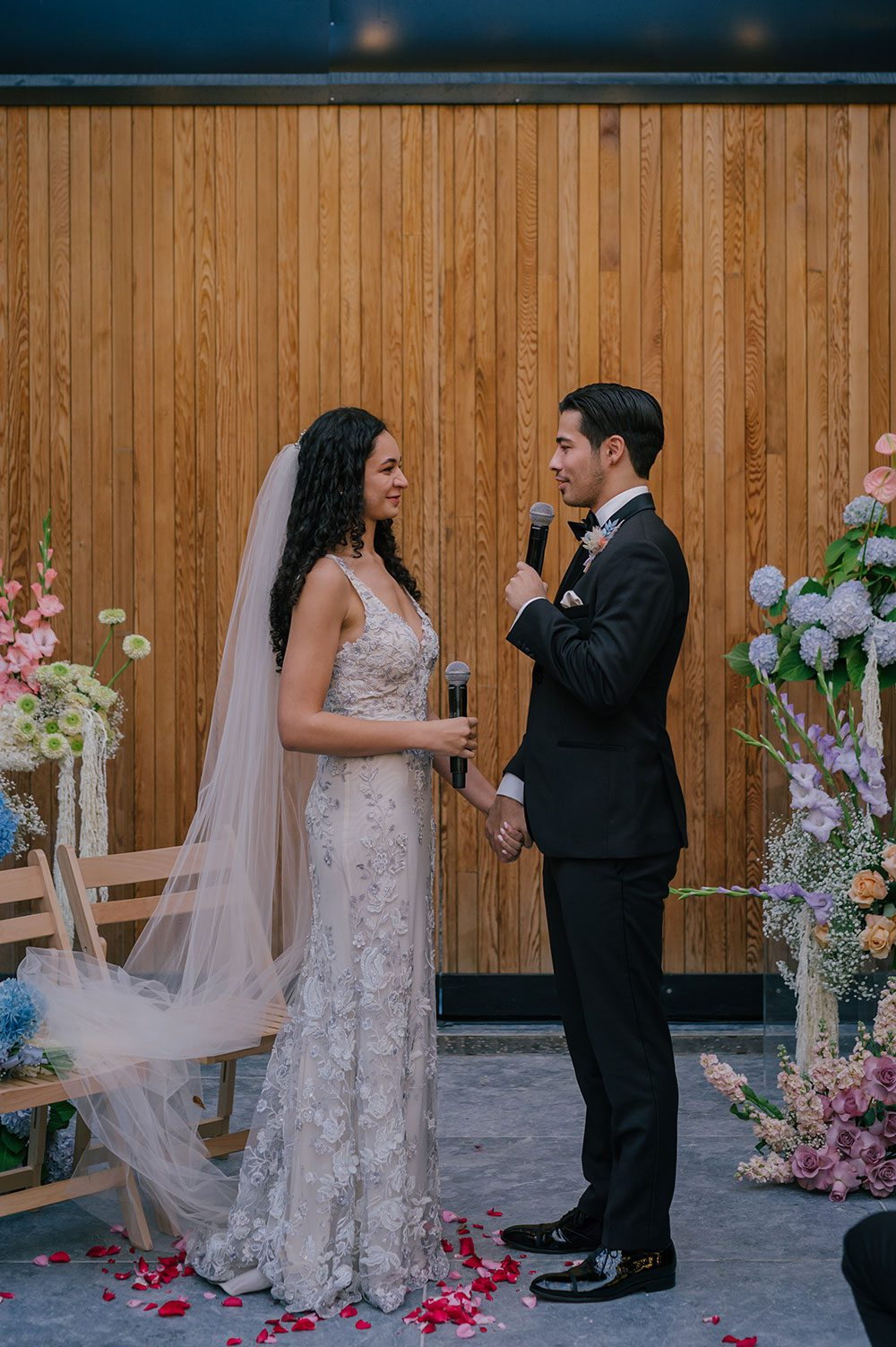 Bride wearing Kazumi Gown in soft grey with hand embellished lace and a low back - saying vows